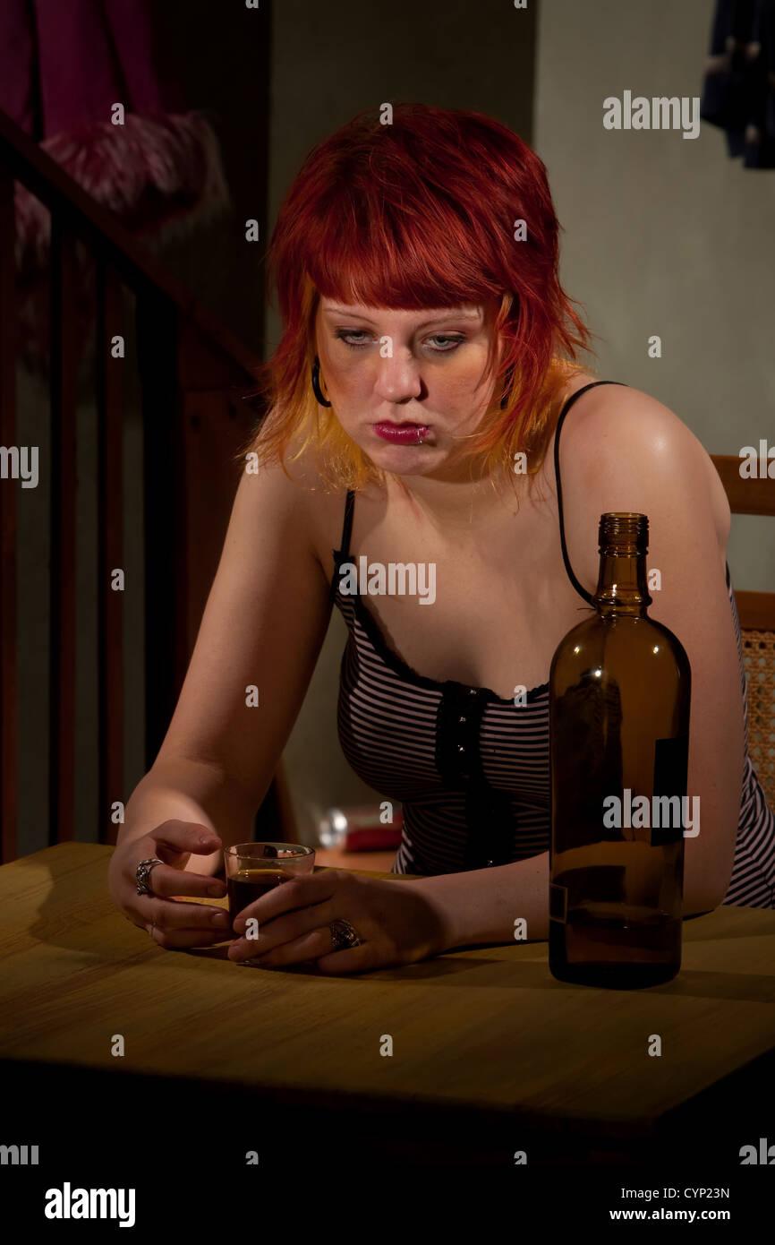 Underage alcoholic woman with bottle of wine - Stock Image