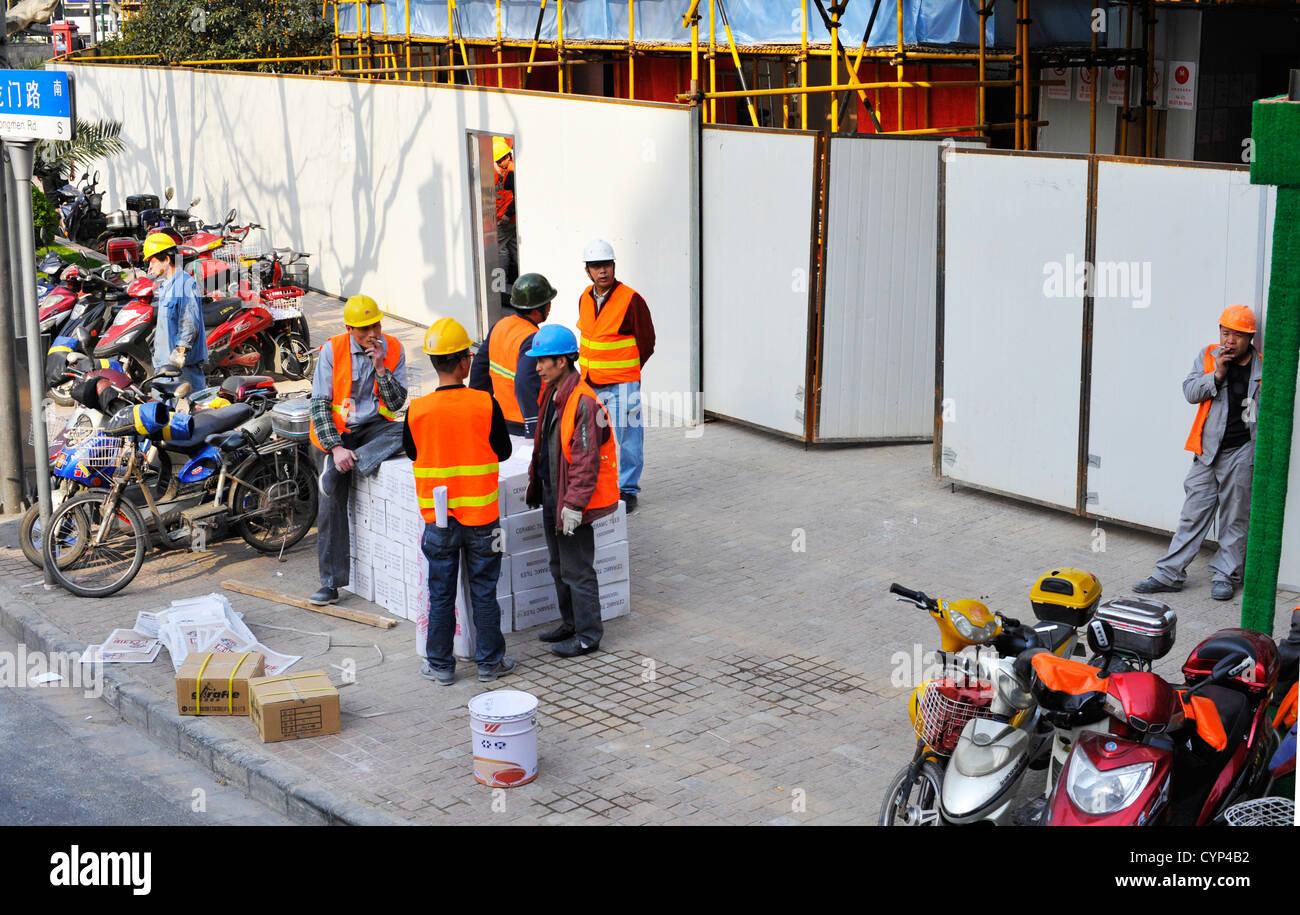 Workmen chatting in Shanghai. - Stock Image