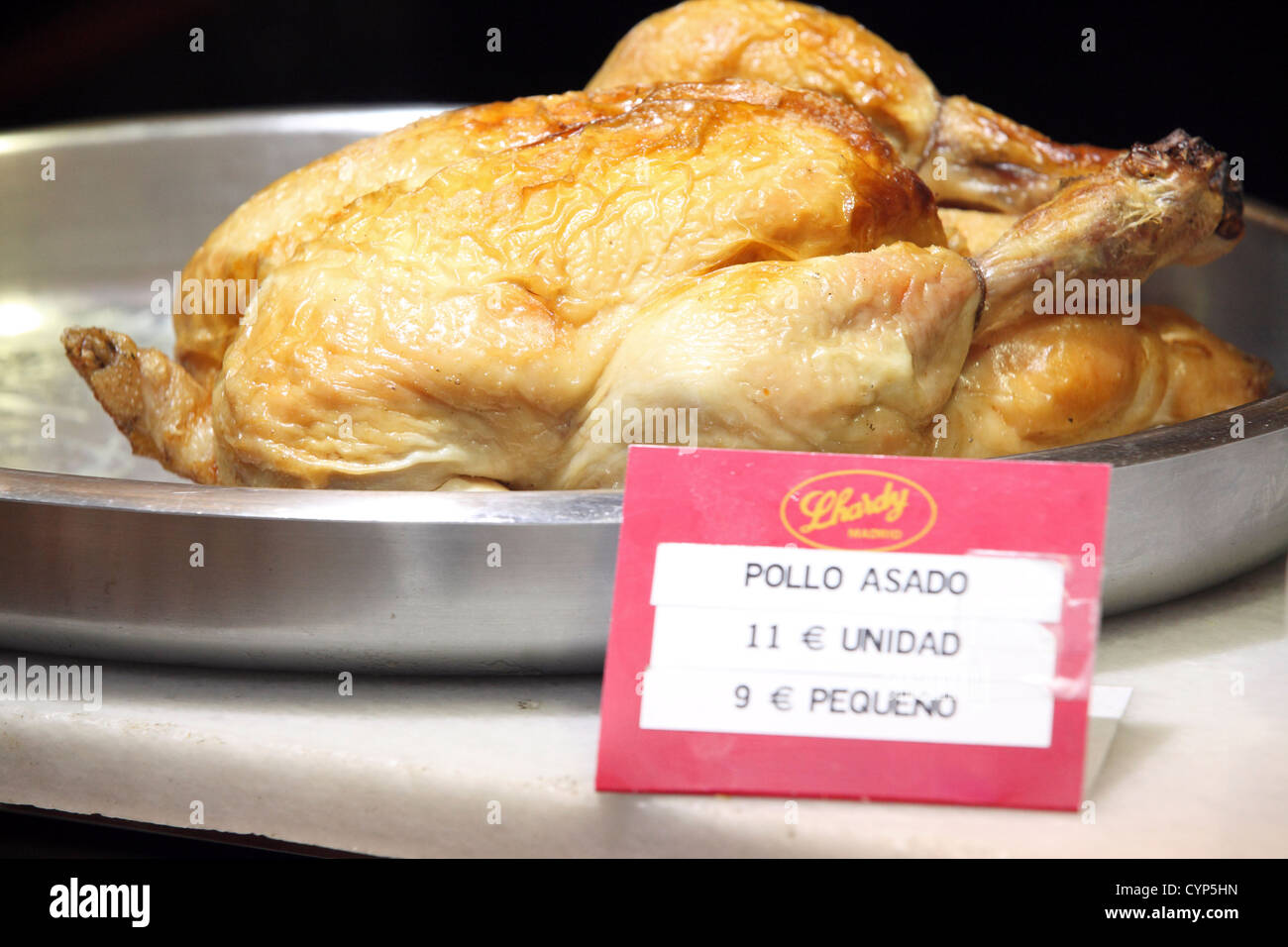 Whole roast chicken for sale in Spanish shop window, price