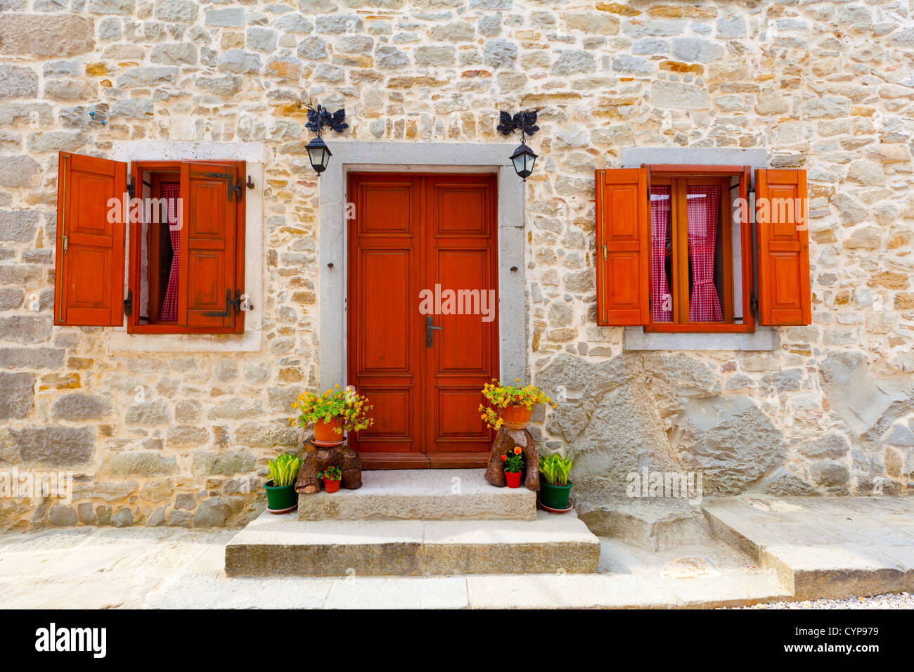 House With Wooden Windows And Doors Surrounded In The Stone Wall