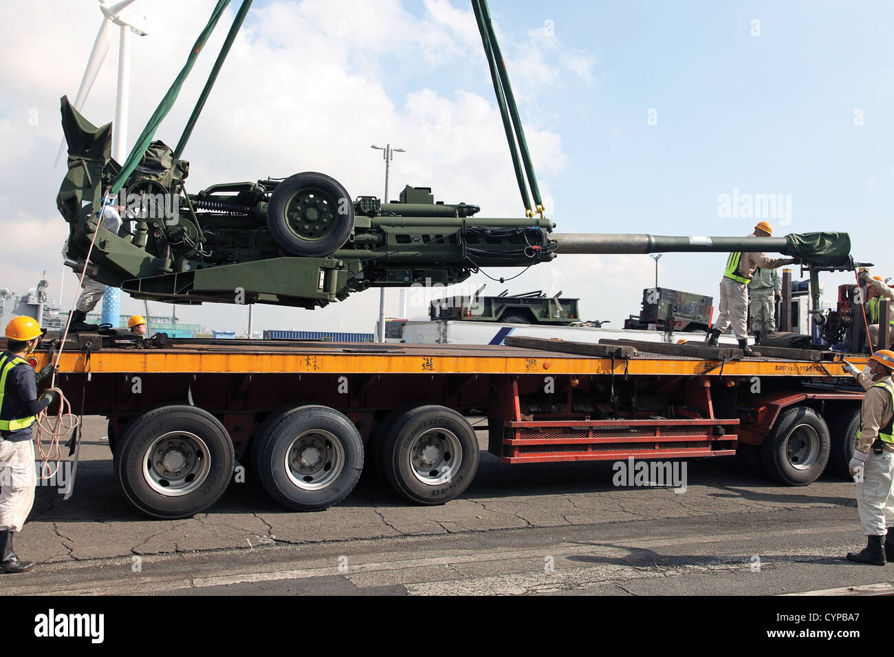 An M777A2 155 mm howitzer is loaded onto a trailer Nov. 7 at Yokohoma Port, Tokyo. Howitzers and other equipment - Stock Image
