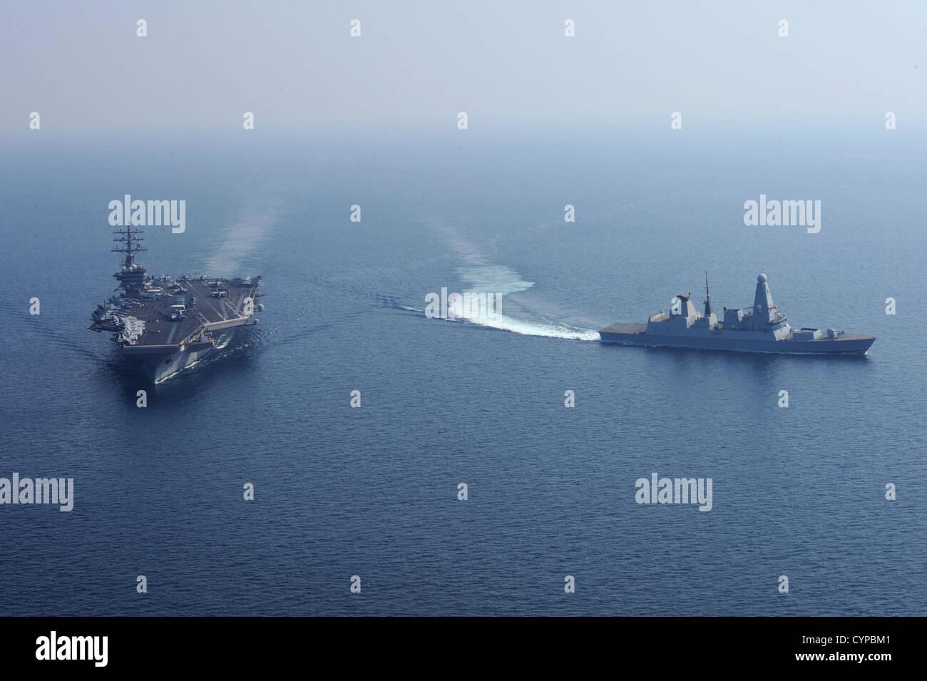 The Royal Navy destroyer HMS Diamond (D34) turns away from the aircraft carrier USS Dwight D. Eisenhower (CVN 69). - Stock Image