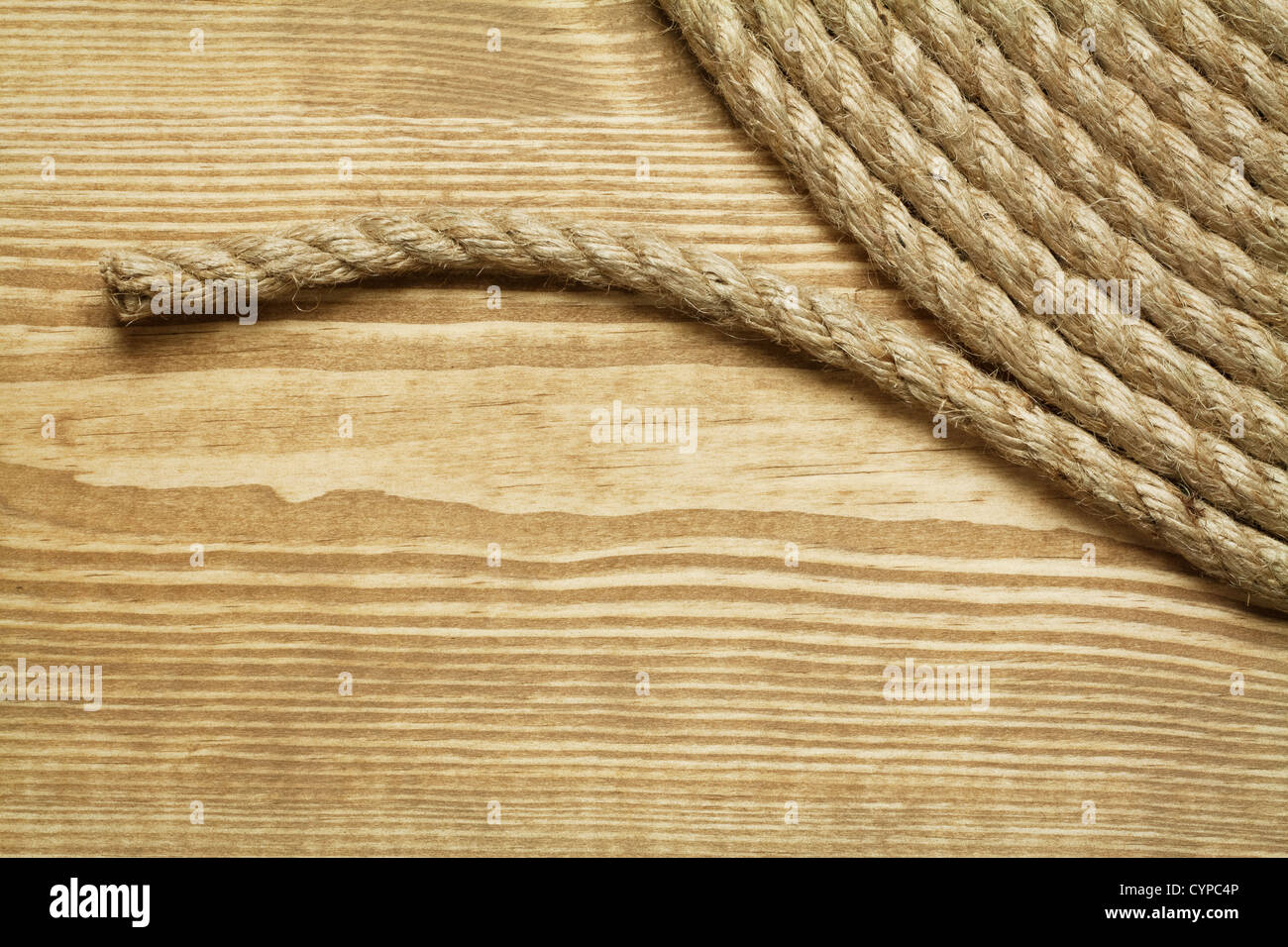 Roll of rough rope on wooden background - Stock Image