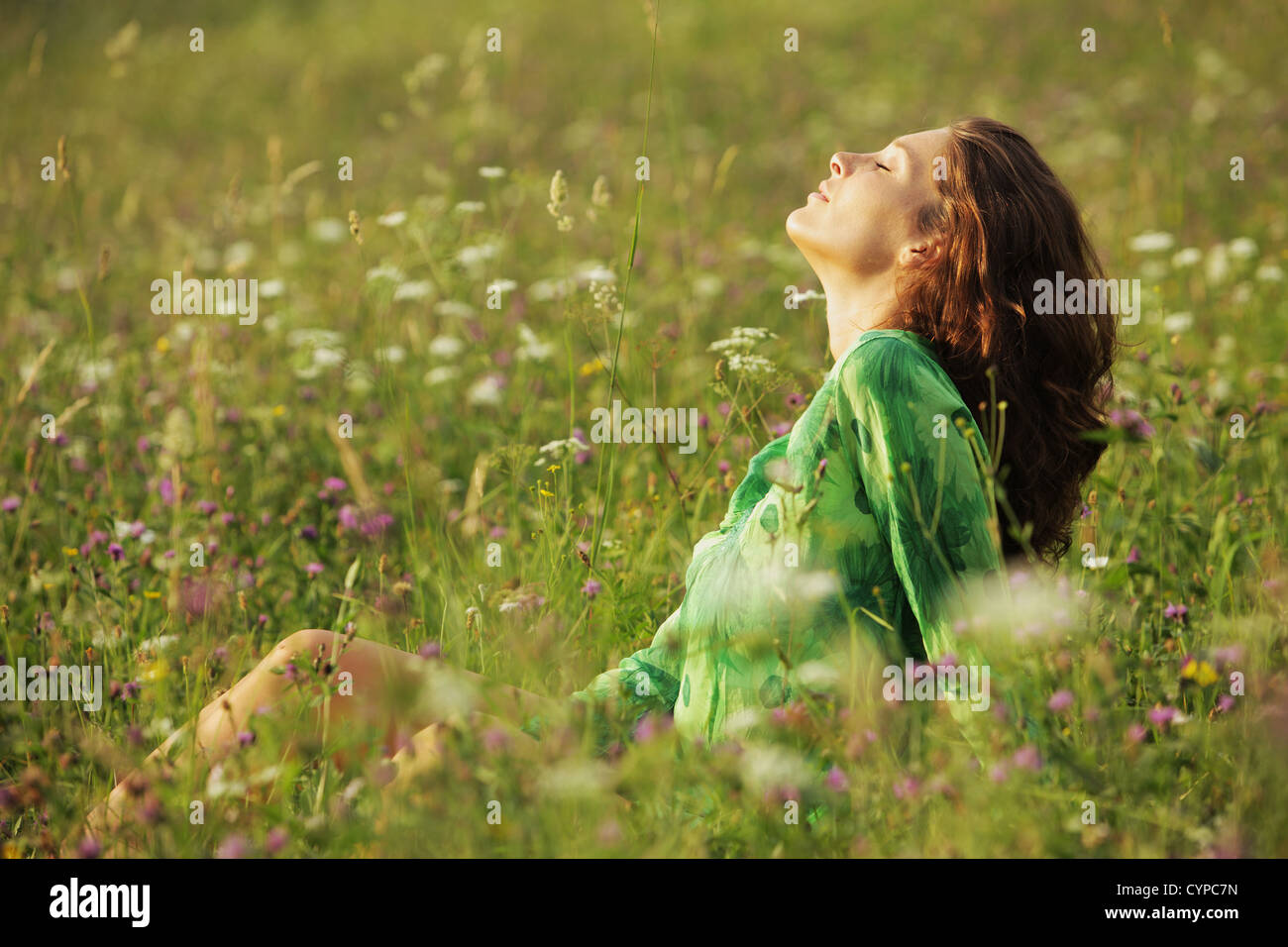 Young beautiful woman enjoying nature in the flowers field - Stock Image
