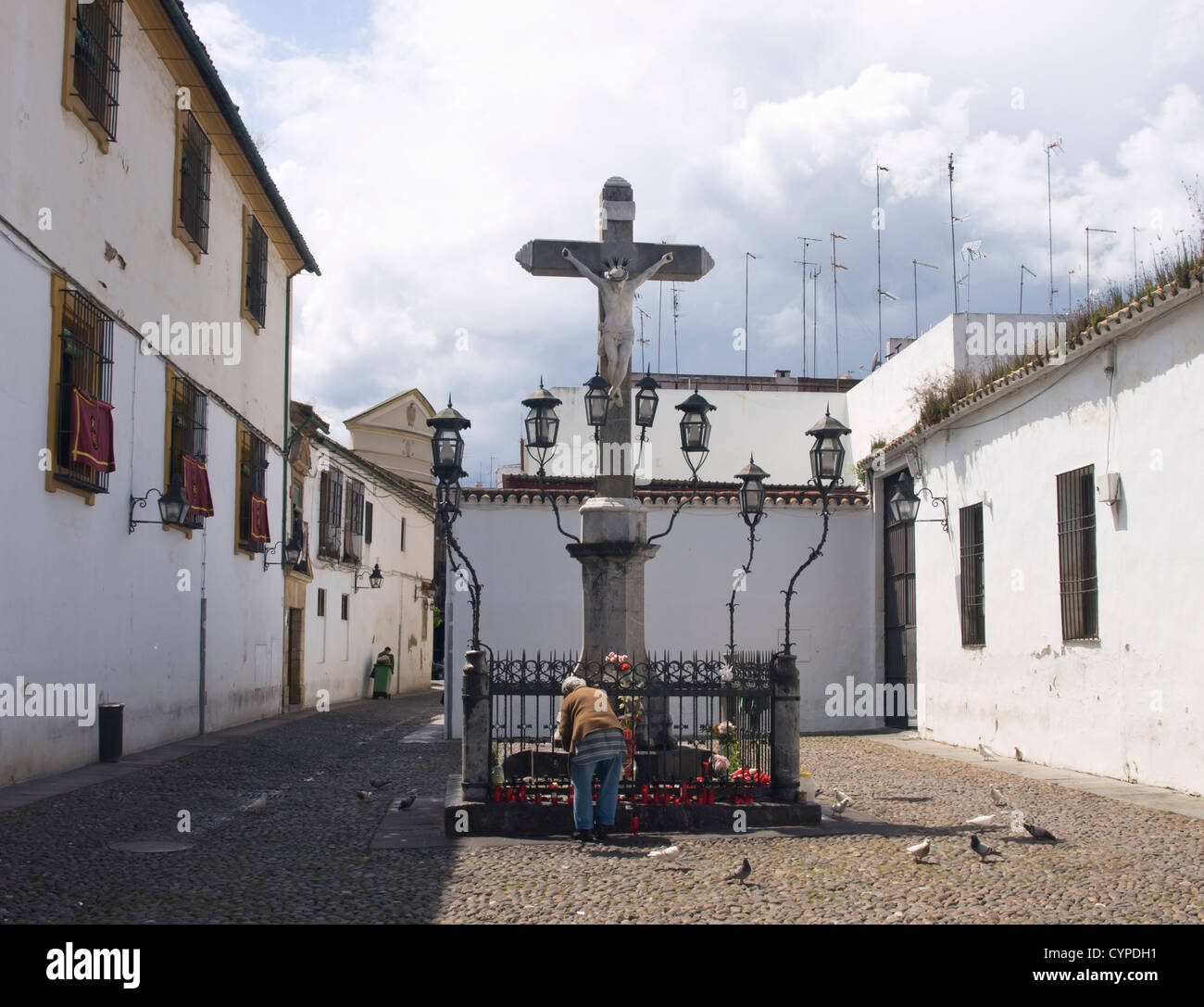 Calvary in stone with worshiper arranging flowers, Plaza de los Capuchinos, Cordoba Andalusia Spain - Stock Image