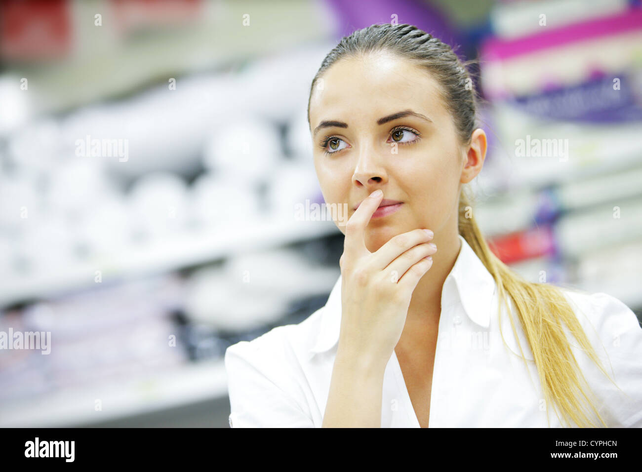 Beautiful blonde, hand to lips, chooses product in supermarket - Stock Image