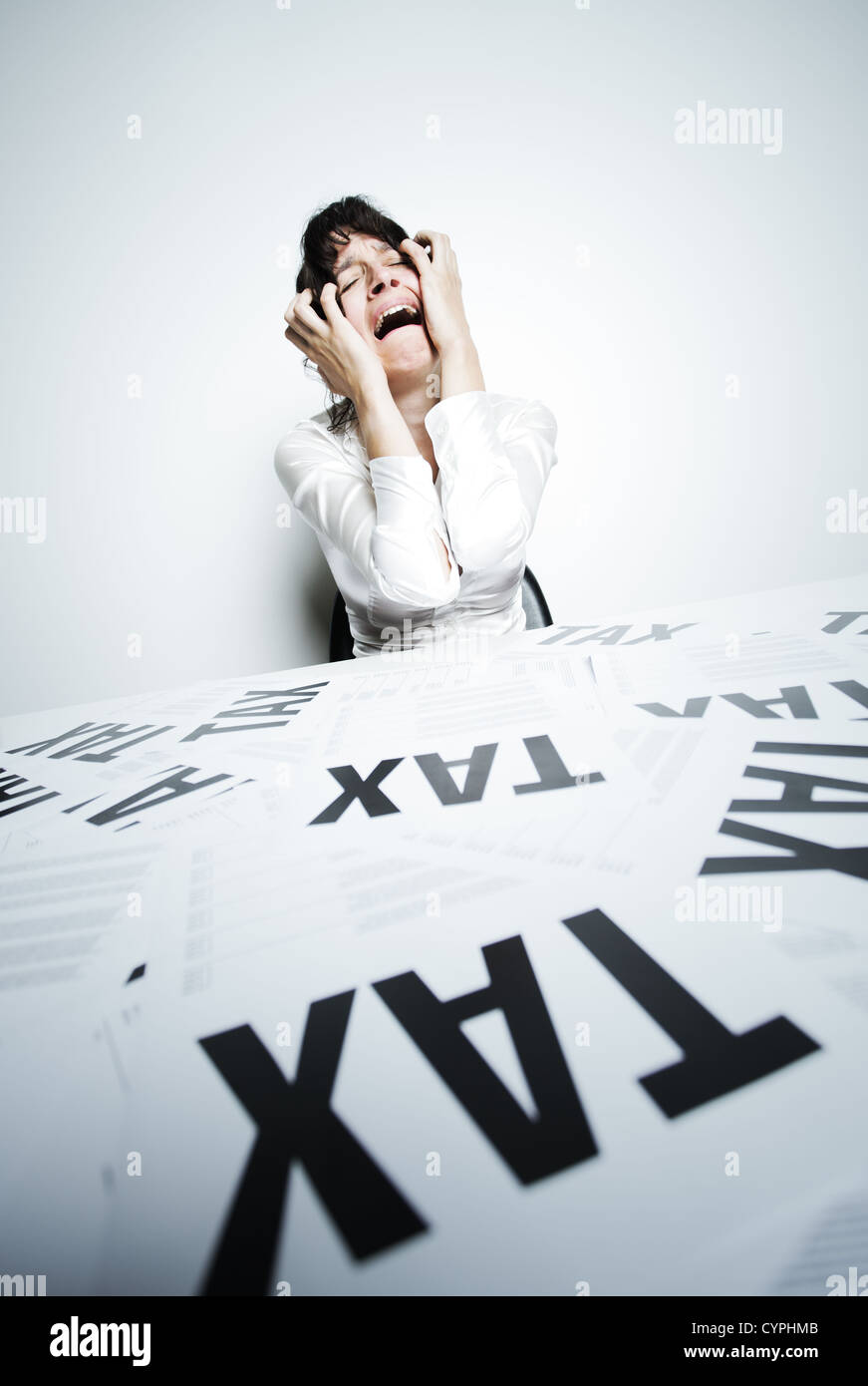 Desperate woman at her taxes-paperwork covered desk to crying bitter tears with her hands on face - Stock Image