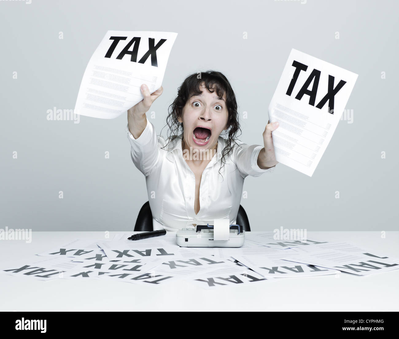 Young desperate woman at her desk showing terrible tax bills to the camera while shouting out - Stock Image