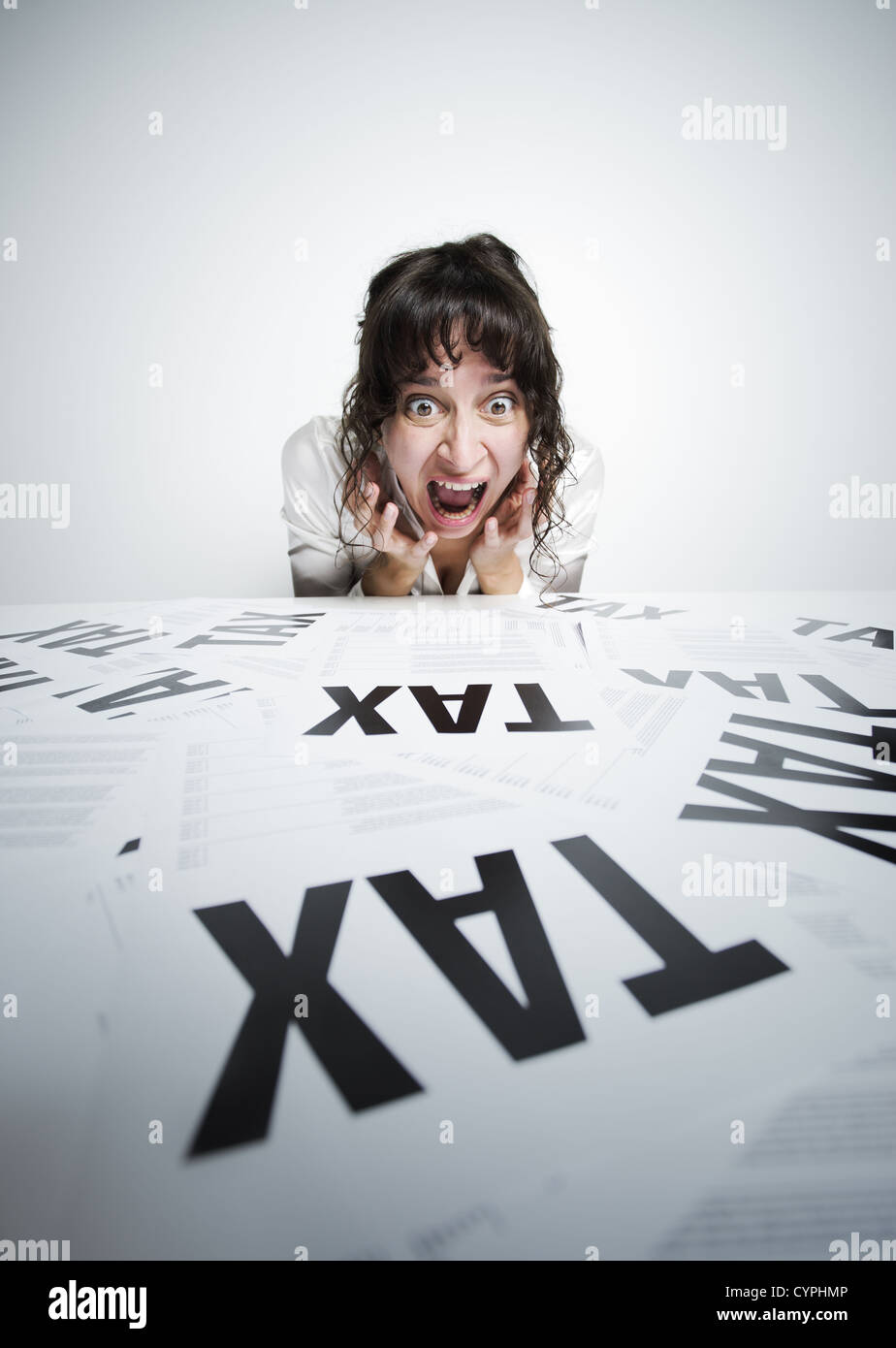 Astonished woman looking at a bunch of worrying tax forms on her desk - Stock Image