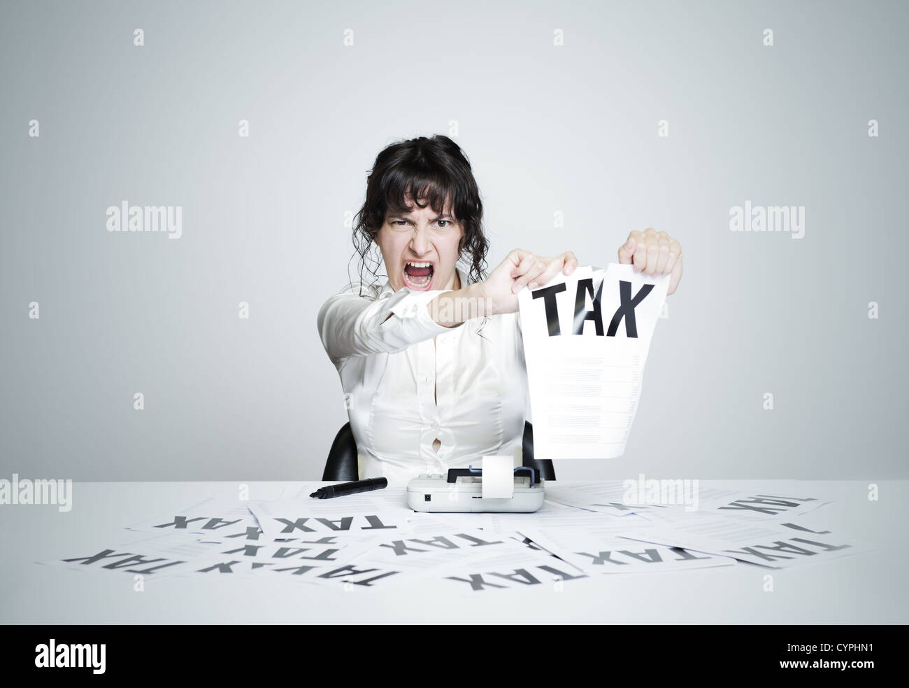 Young desperate woman at her paperwork-covered desk ripping up a tax form staring at the camera - Stock Image