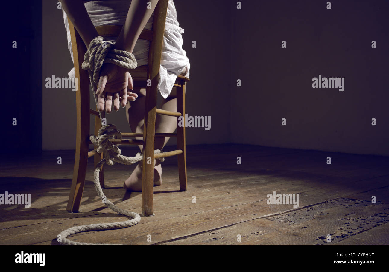 Young woman tied to a chair in a empty room - Stock Image