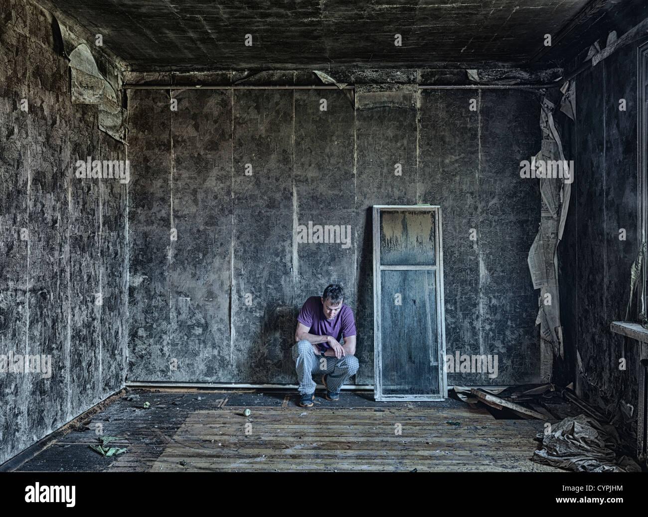 sad man, sitting  in burnt  room - Stock Image