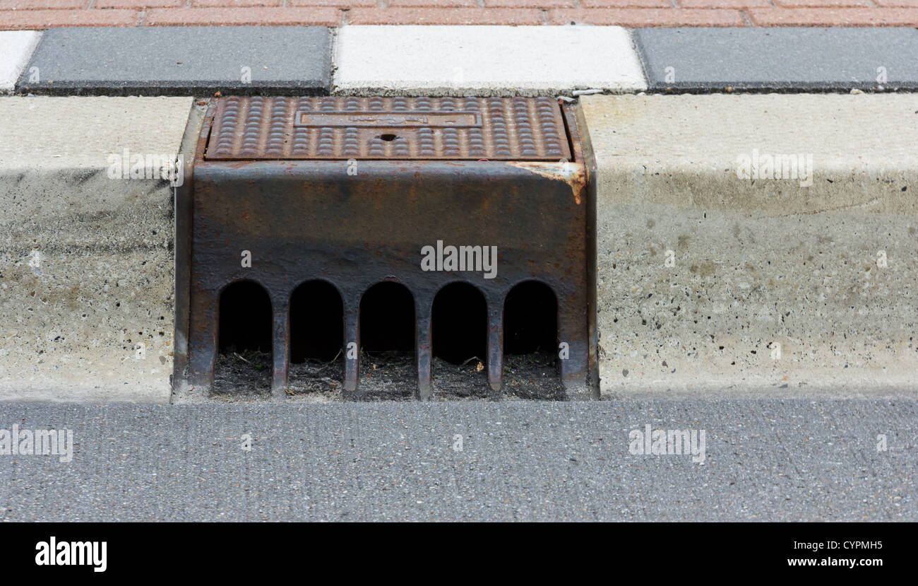 Sidewalk with a street drainage and road - Stock Image