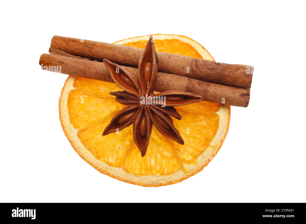 Christmas associated flavors of dried orange, with cinnamon and star anise laid on top isolated against white - Stock Image