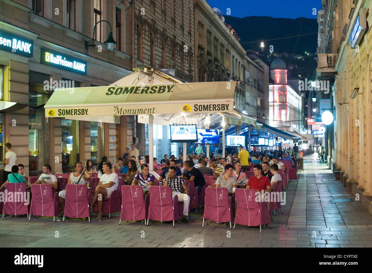 Dusk view of patrons at a sidewalk cafe in the Baščaršija (bazaar) in Sarajevo in Bosnia Herzegovina. - Stock Image