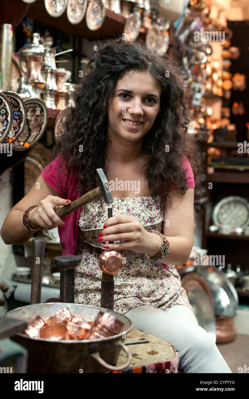 A coppersmith in her shop in the Sarajevo Baščaršija (bazaar) in Bosnia Herzegovina. - Stock Image