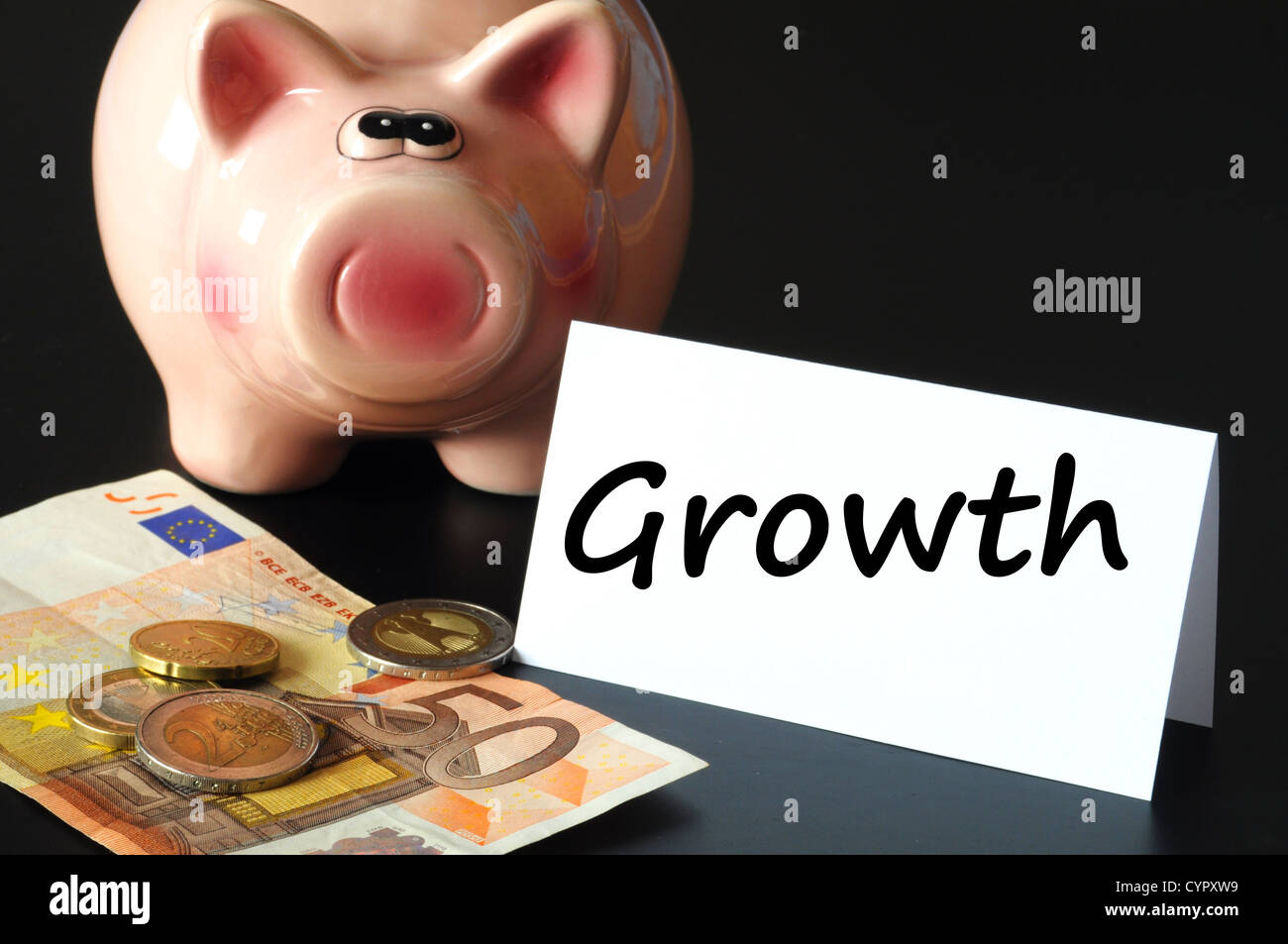 financial or economic growth concept with piggy bank on black background - Stock Image
