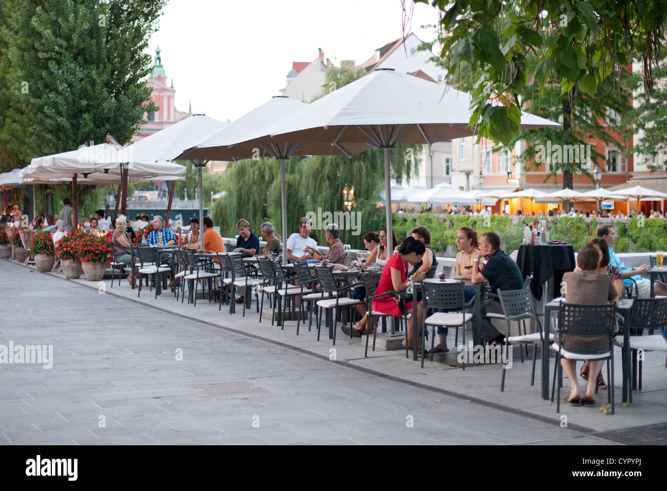 Sidewalk cafés on the banks of the Ljubljanica River in the old town in Ljubljana, the capital of Slovenia. - Stock Image