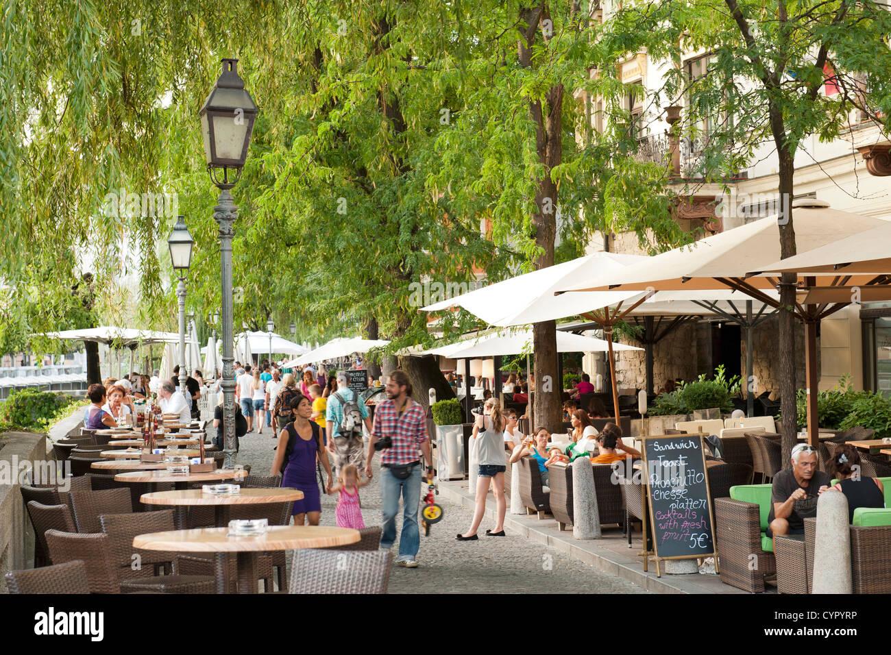 Sidewalk cafés on the banks of the Ljubljanica River in the old town in Ljubljana, the capital of Slovenia. - Stock Image