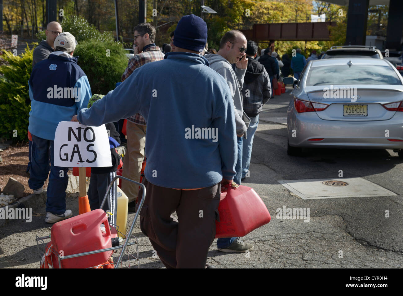 Line at gas station after Hurricane Sandy, northern NJ.  People with cans waiting to get gas for cars and generators. - Stock Image
