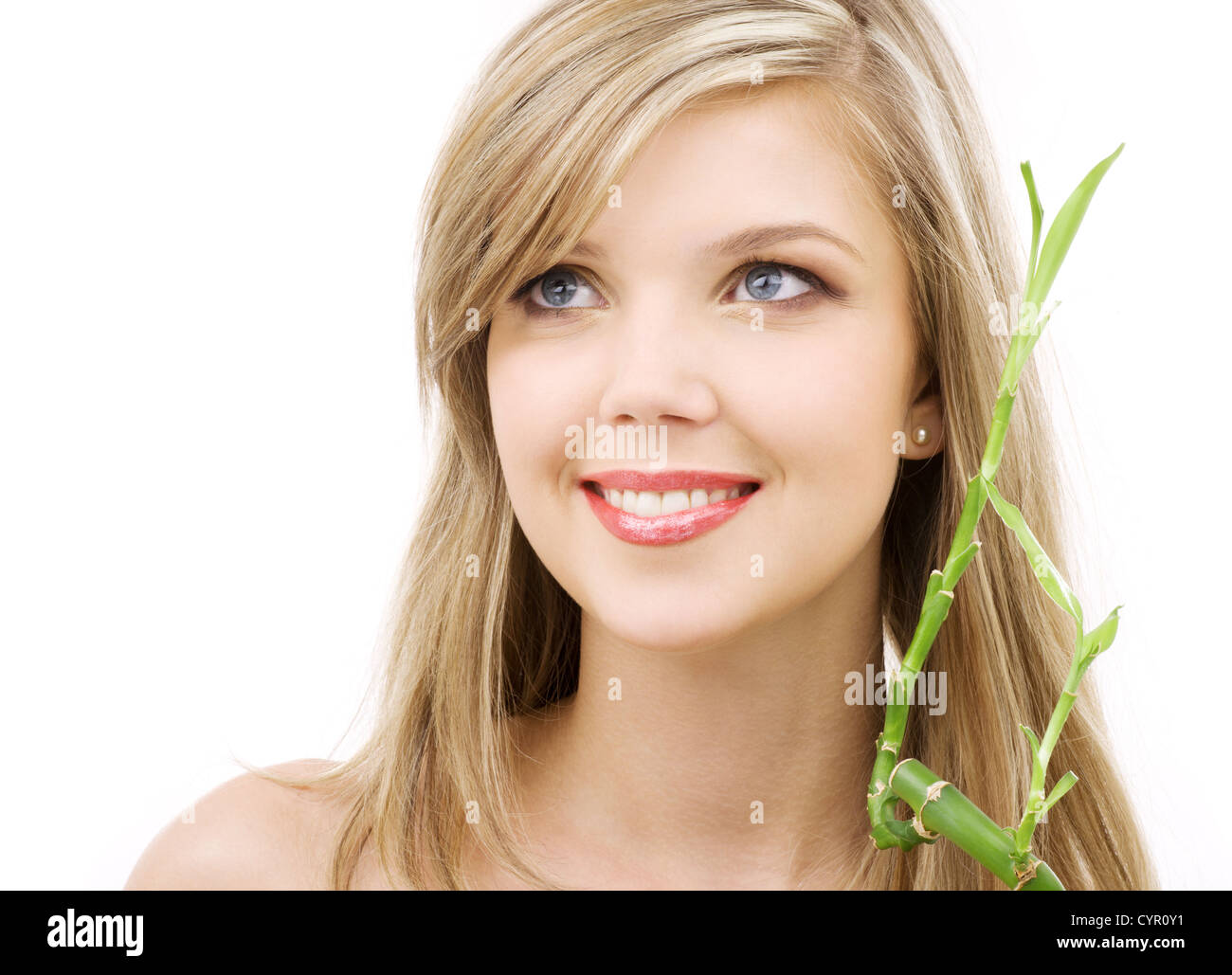 picture of lovely blue-eyed blonde with bamboo - Stock Image
