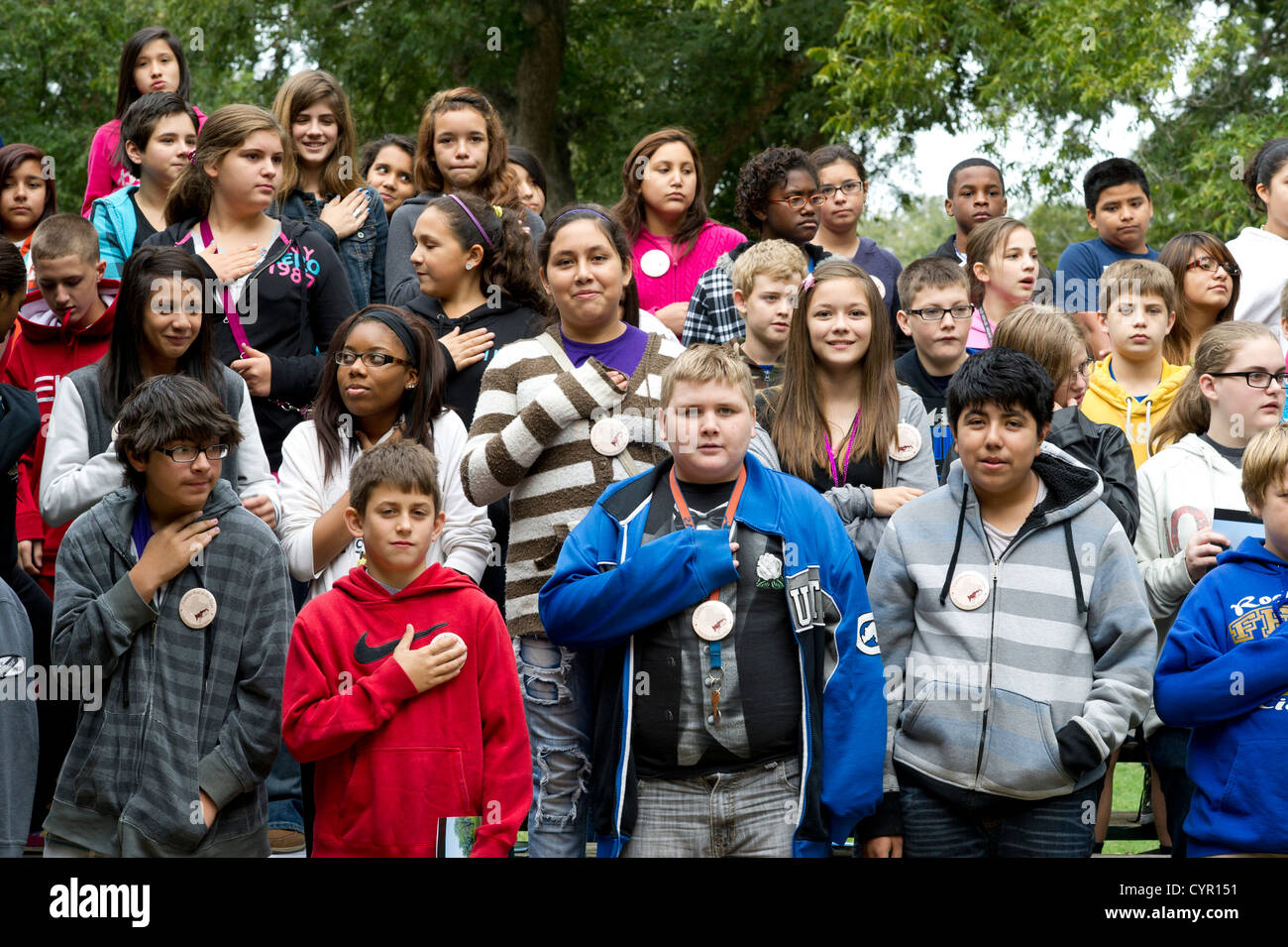 Multicultural group of Texas junior high school students recite Pledge of Allegiance during field trip to rural - Stock Image