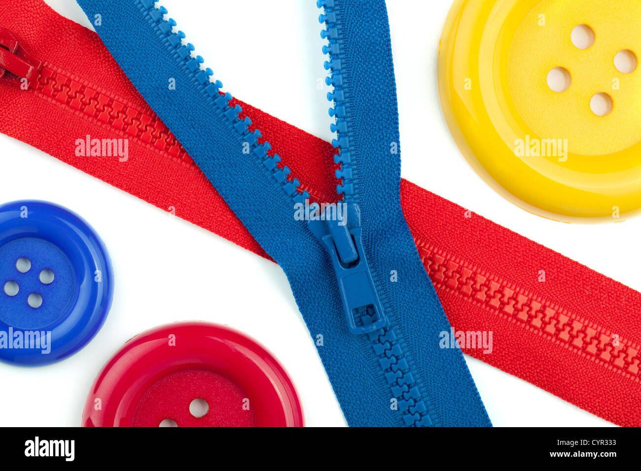 Three colored sewing buttons and two zippers closeup. Isolated on white Stock Photo