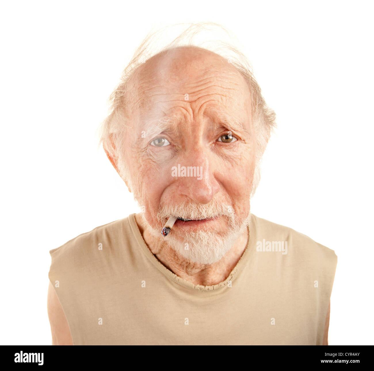 Indigent senior man in ragged sgirt smoking cigarette - Stock Image