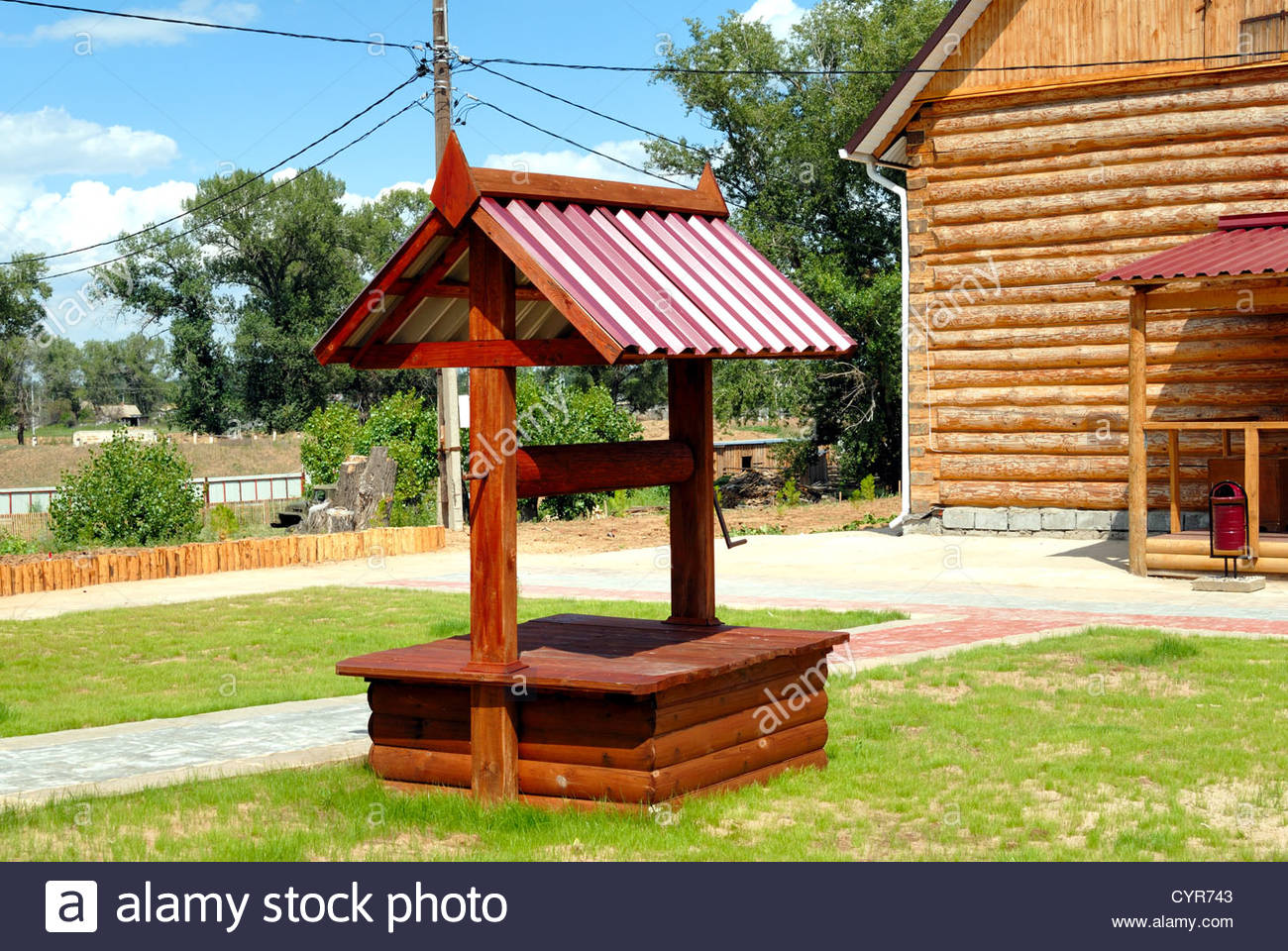 Wooden well stylised semi-antique against a rural landscape - Stock Image