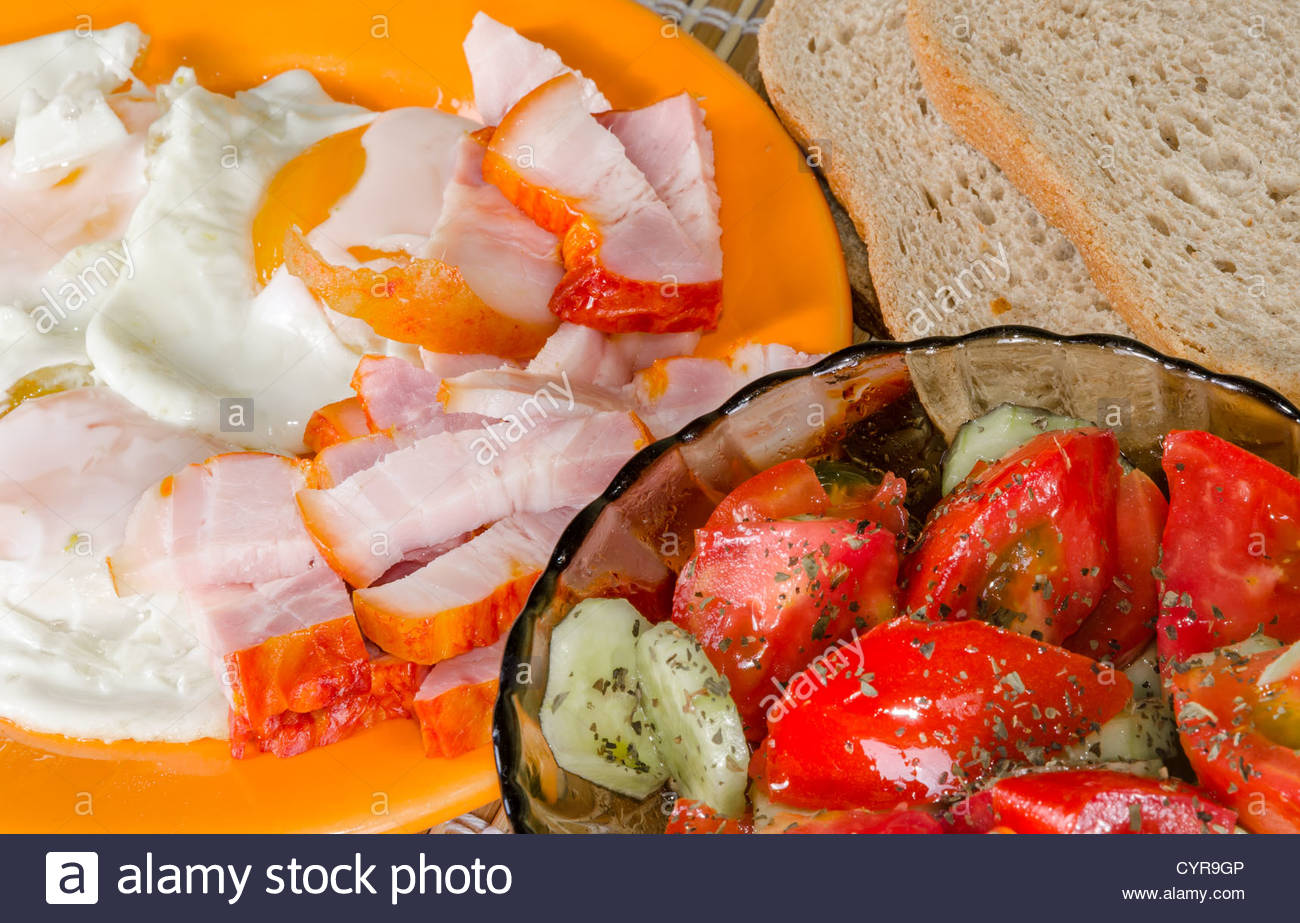 Fried eggs breakfast with salad and bacon - Stock Image