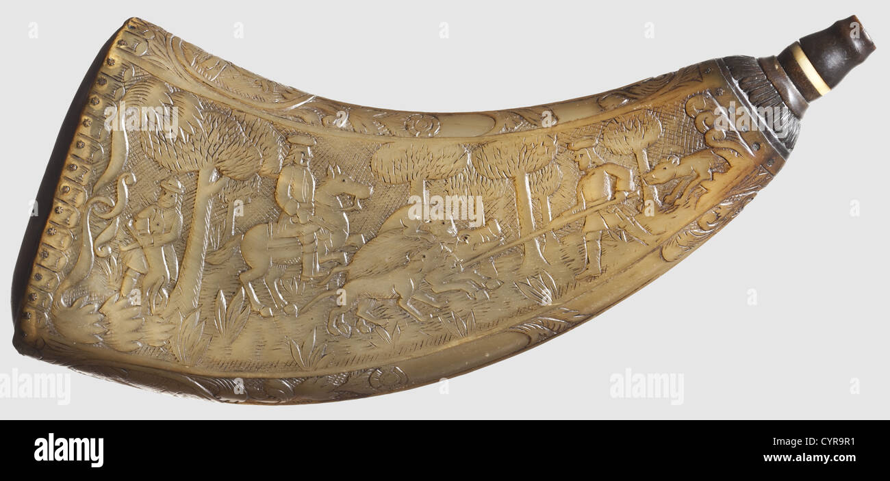 A carved powder horn, dated 1806 Compressed horn carved in relief on both sides, displaying hunting parties after - Stock Image