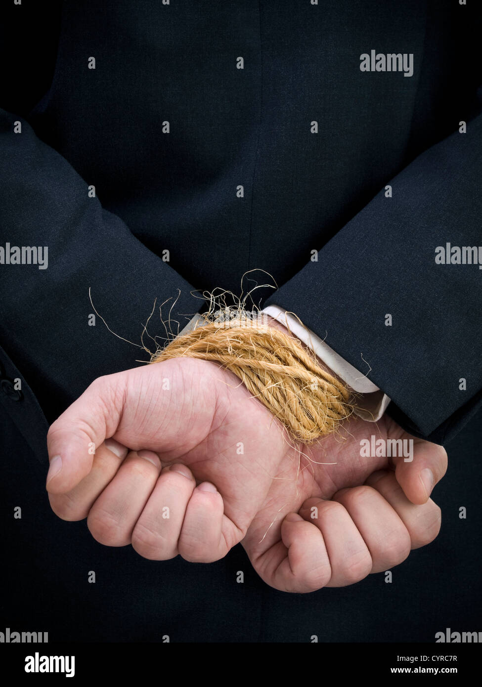 Closeup on a businessman's tied up hands. - Stock Image