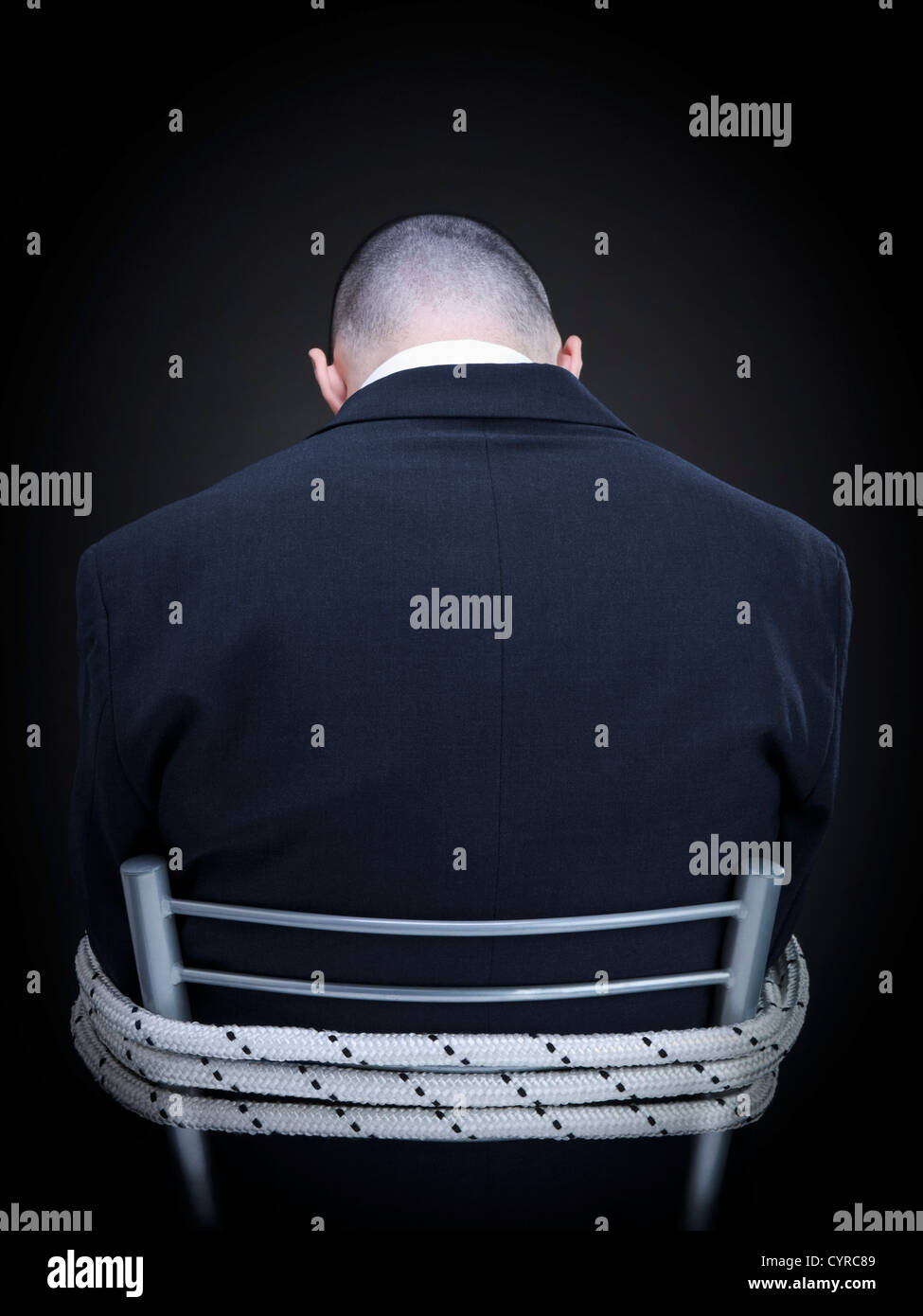 A businessman is tied up on a chair turning his back to the camera. - Stock Image