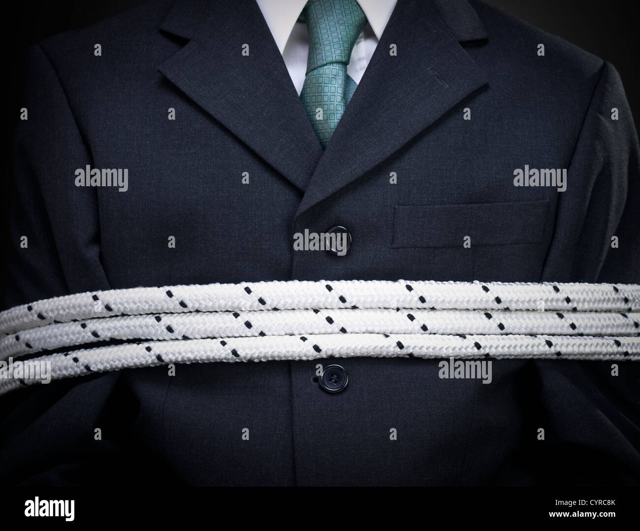 Closeup on the chest of a tied up businessman. - Stock Image