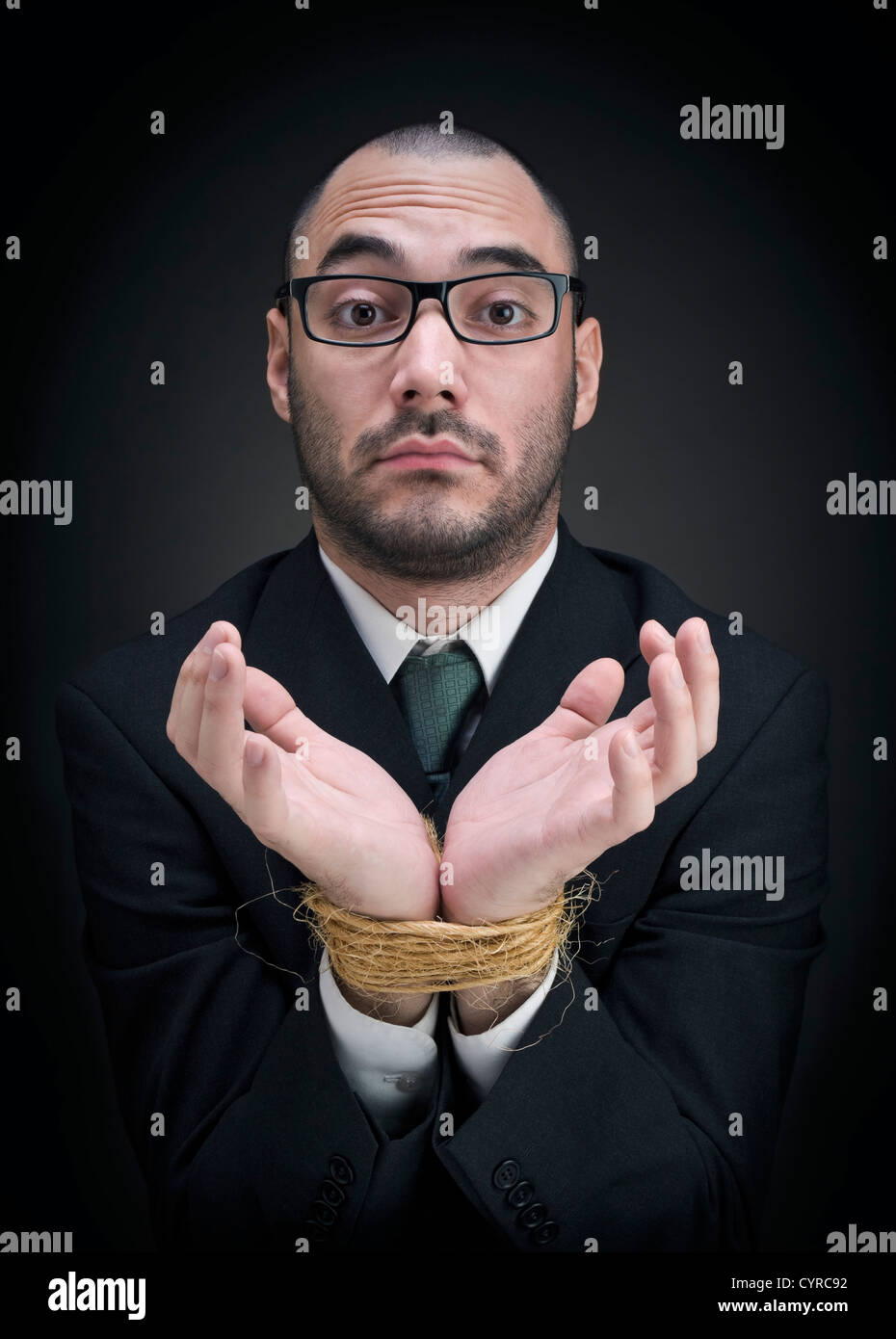A man on a suit shows his tied hands with a puzzled expression. - Stock Image