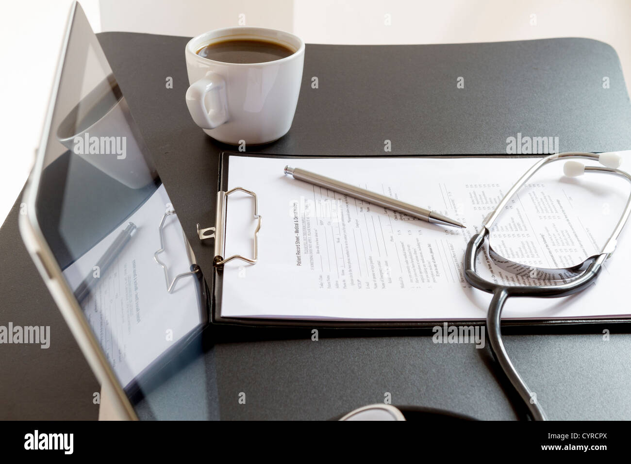 Medical record forms, stethoscope and Tablet PC on the desk - Stock Image