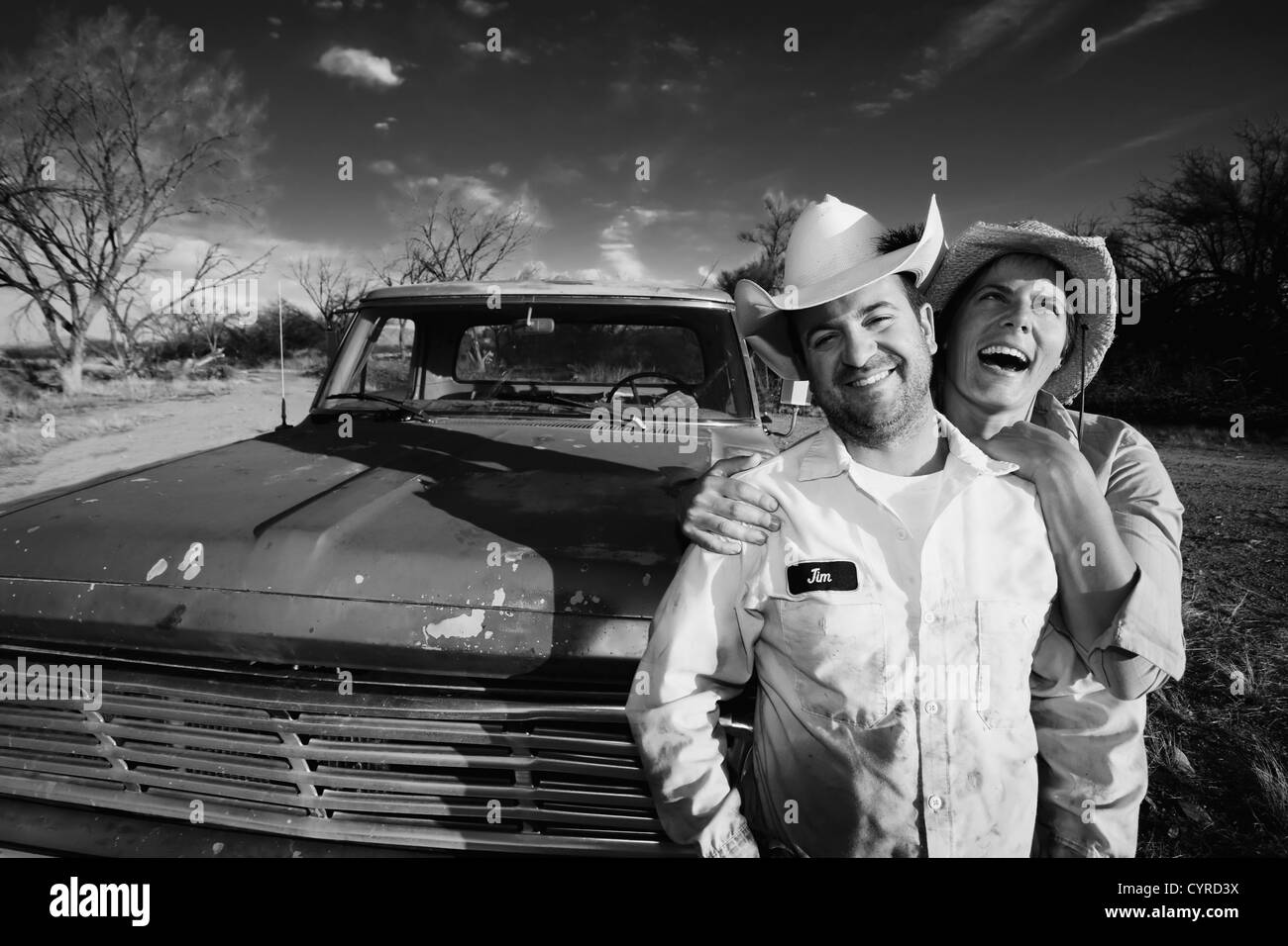 Man and woman in cowboy hats with old truck - Stock Image