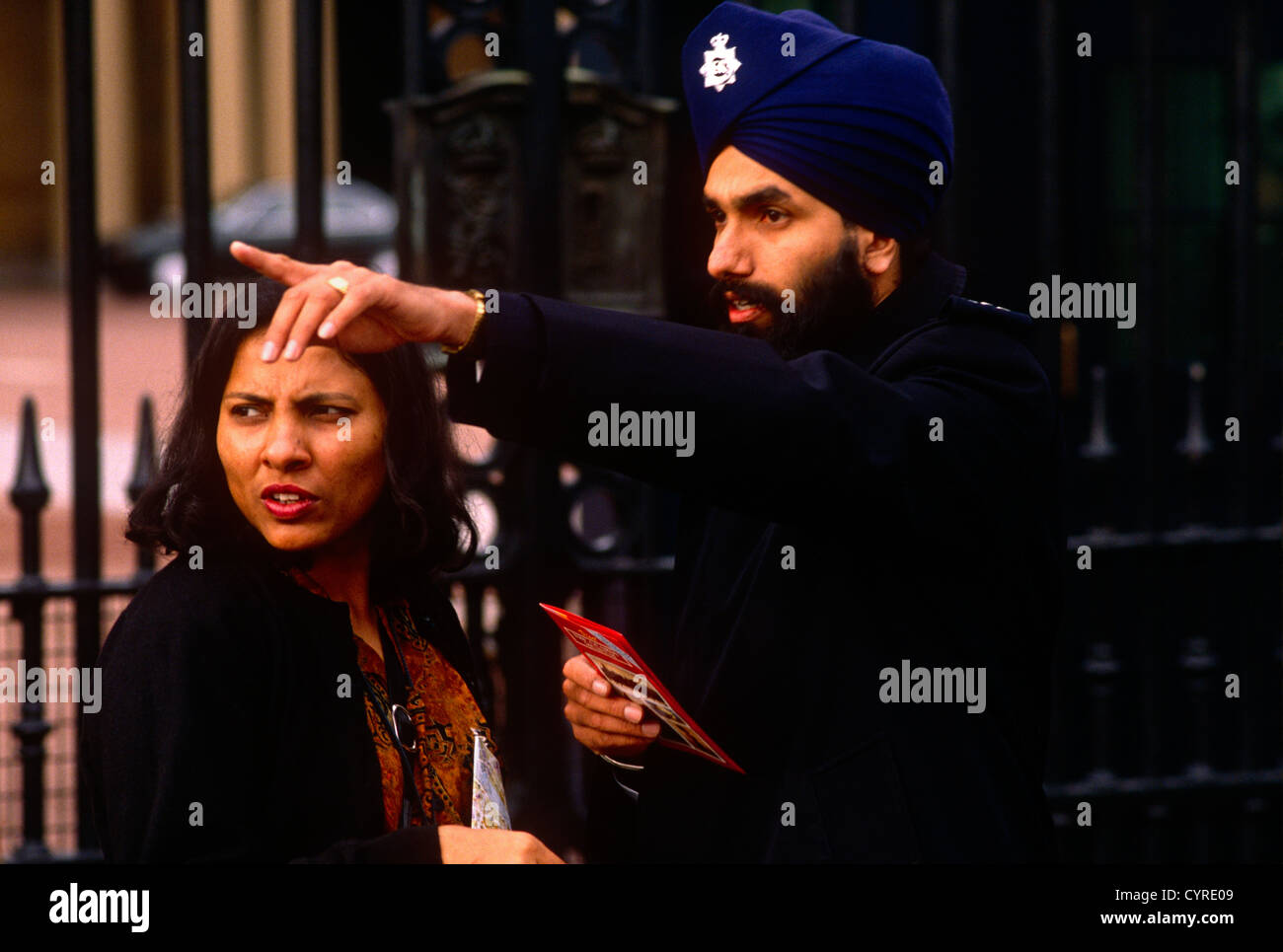 Wearing a turban according to the beliefs of the Sikh faith, a Metropolitan police officer helps an Asian lady citizen - Stock Image