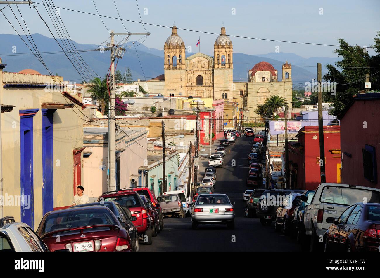 View along street lined by parked vehicles towards church of Santo Domingo American  Hispanic Latin America Latino - Stock Image