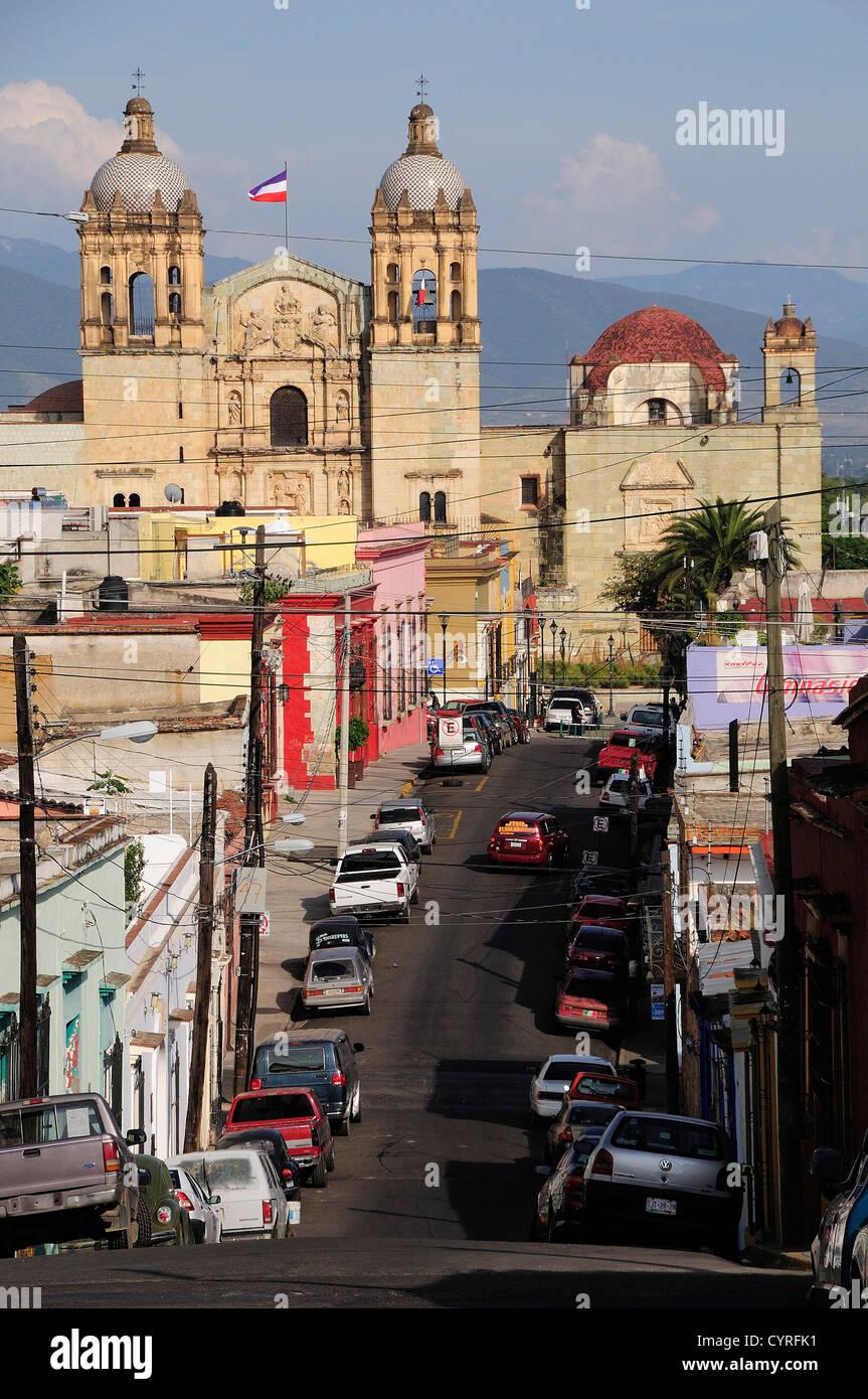View along street lined with parked vehicles towards church of Santo Domingo American  Hispanic Latin America Latino - Stock Image