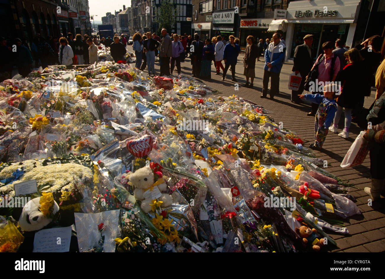 Locals pay respects to a growing mound of a floral memorial in memory of two people killed by an IRA bomb in Warrington - Stock Image
