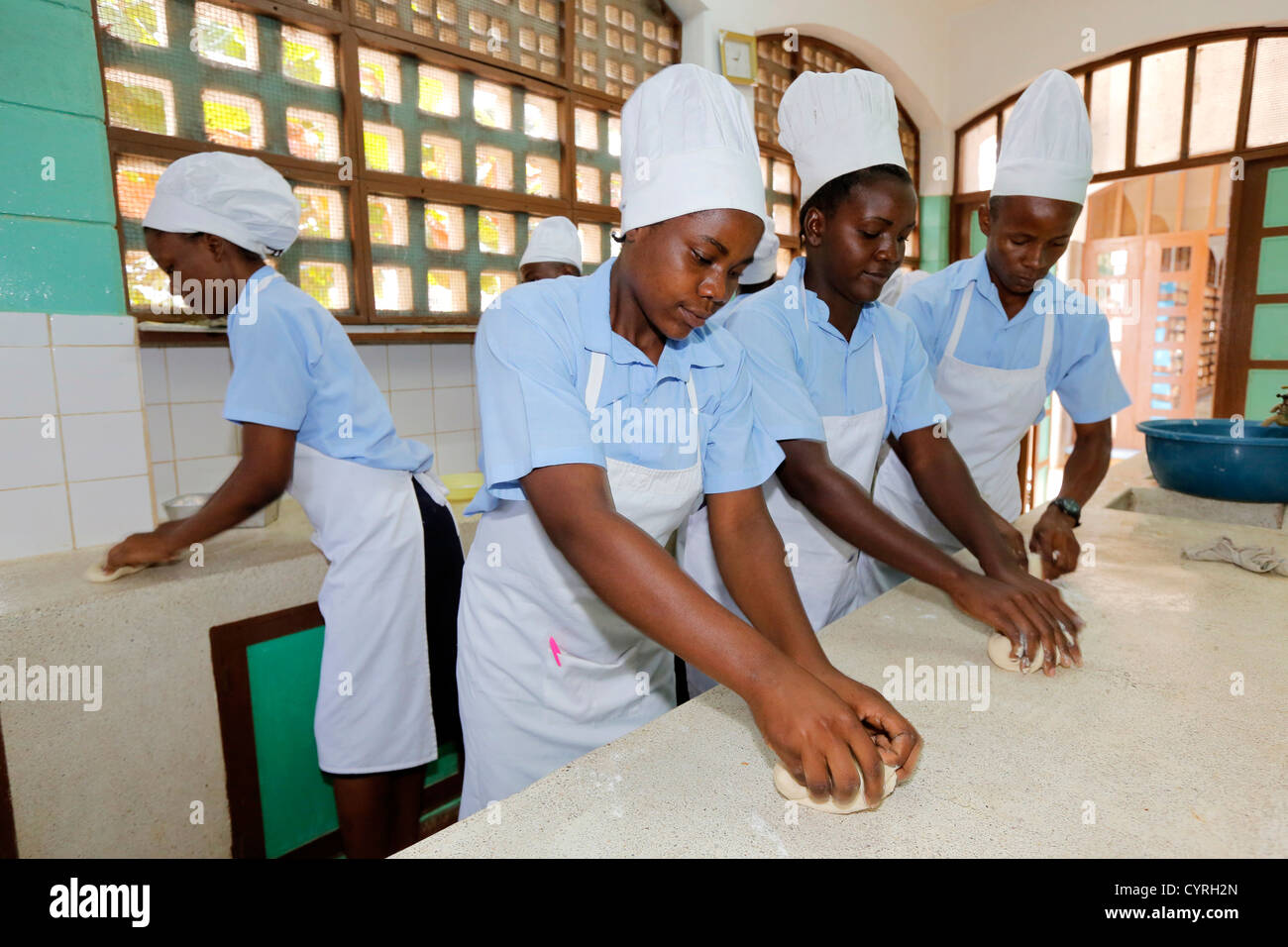 Students learning baking bread in a training bakery kitchen at a vocational training center in Machui, Zanzibar, - Stock Image
