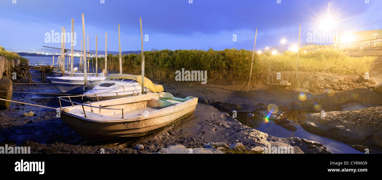 Discard boats on silt of river with city light flare in night. - Stock Image