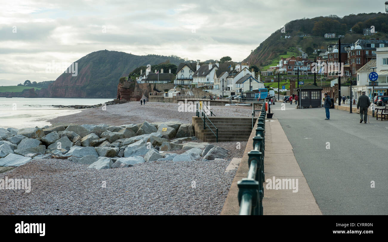 November 6th 2012. Sidmouth, Devon, England. Promenaders along the sea front with the Jurassic coast in the background. - Stock Image