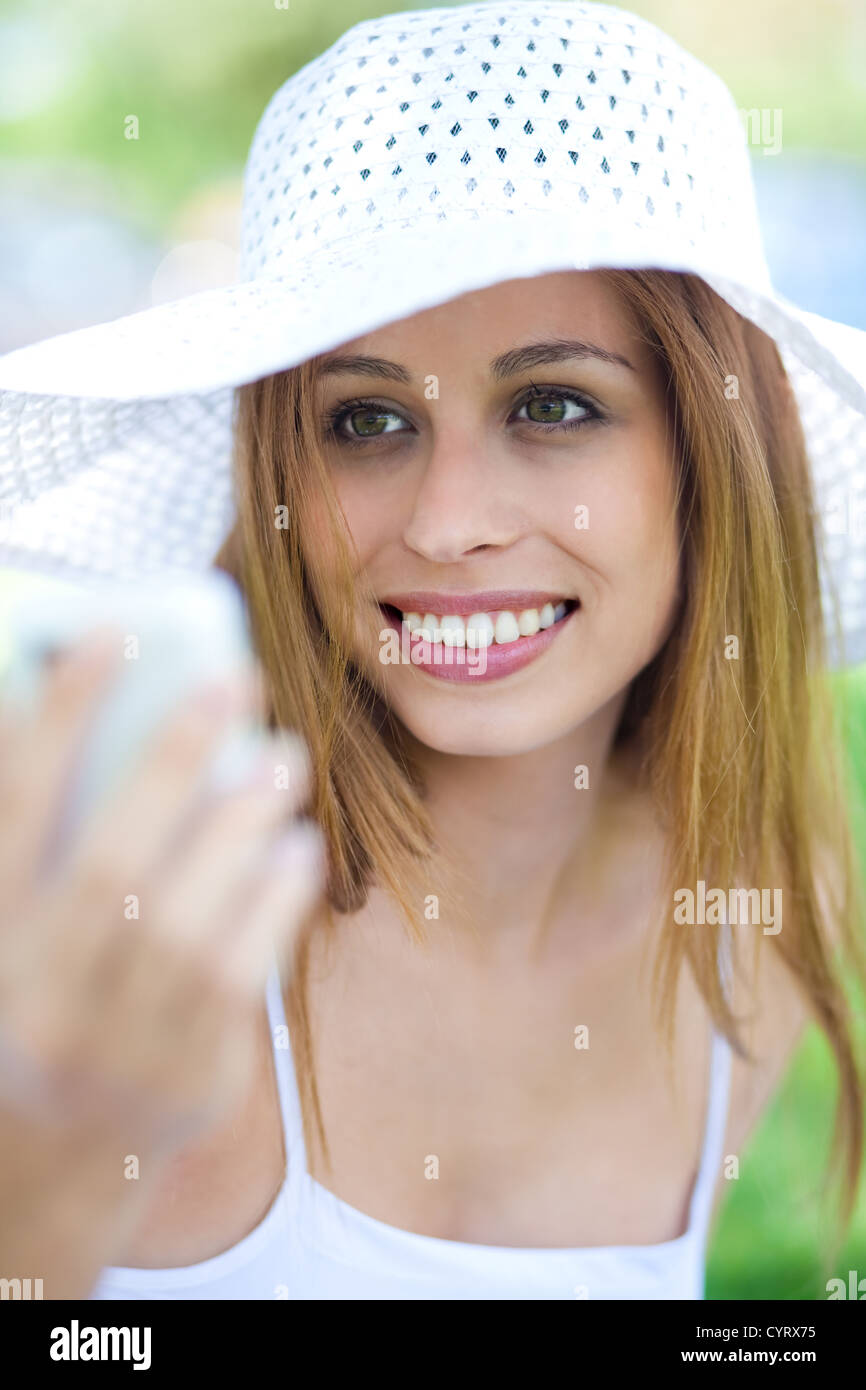 Close up portrait of beautiful smiling women with hat using mobile phone - Stock Image