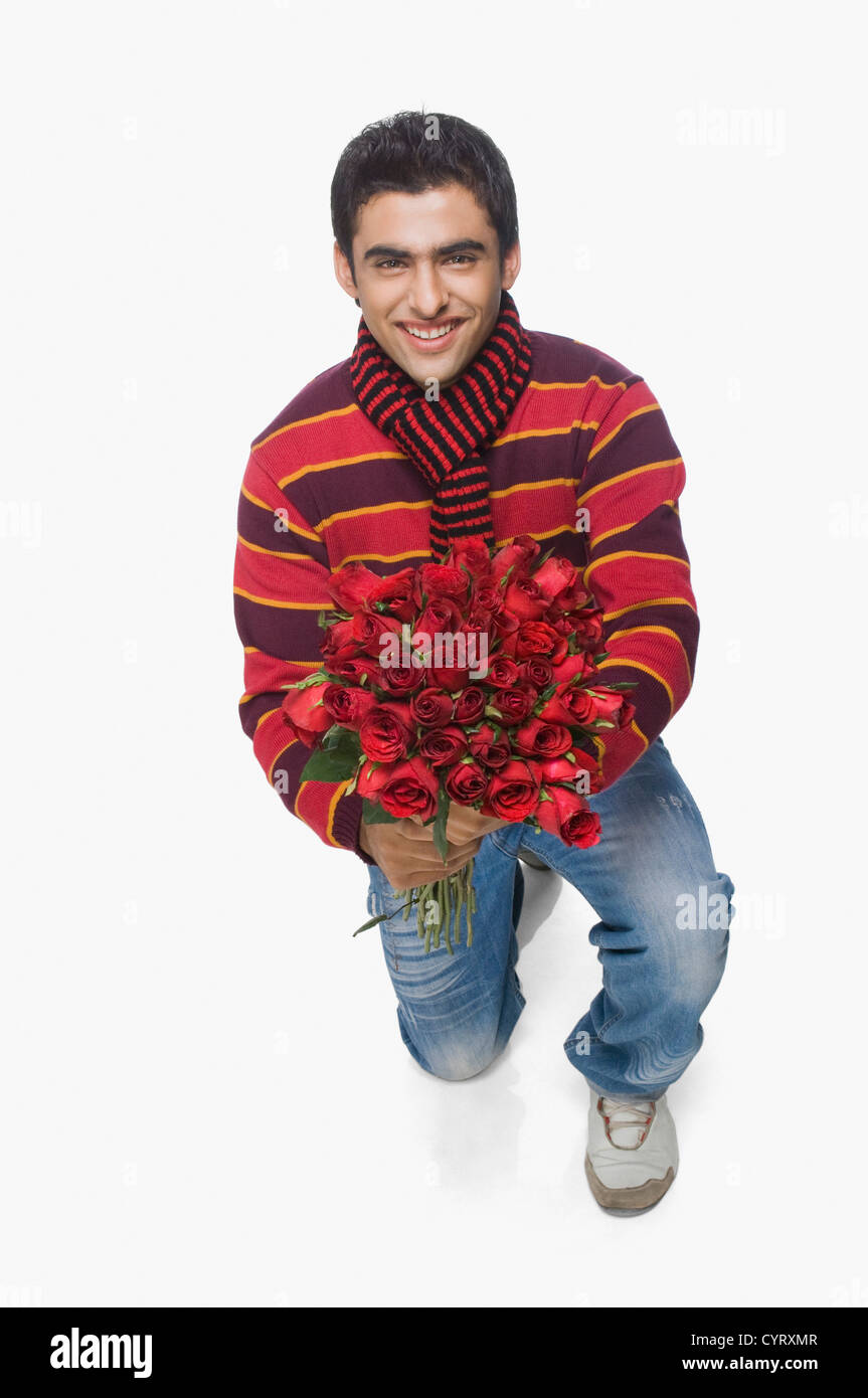 Man holding a bouquet of flowers - Stock Image