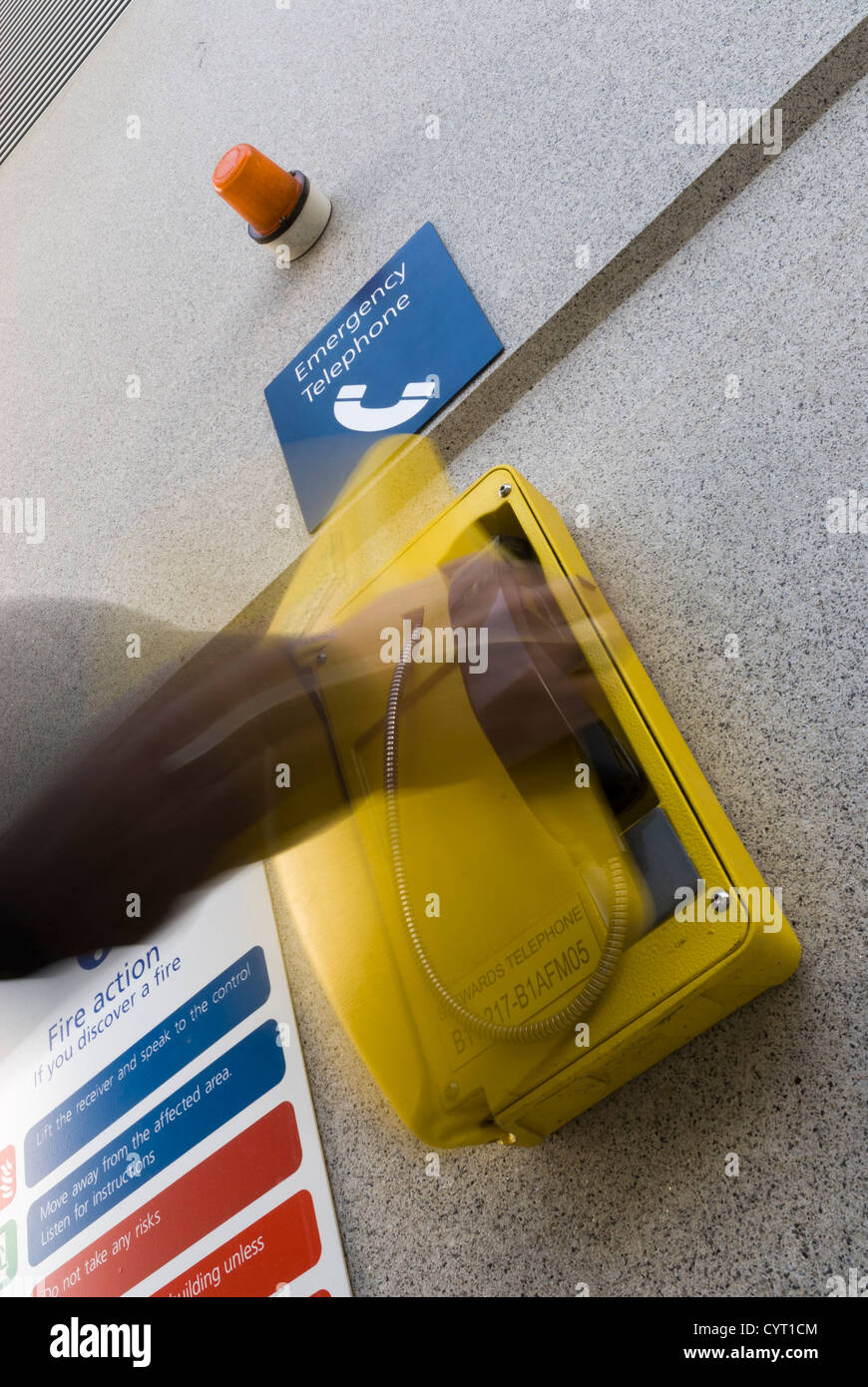 movement of hand reaching for yellow external emergency telephone on wall - Stock Image