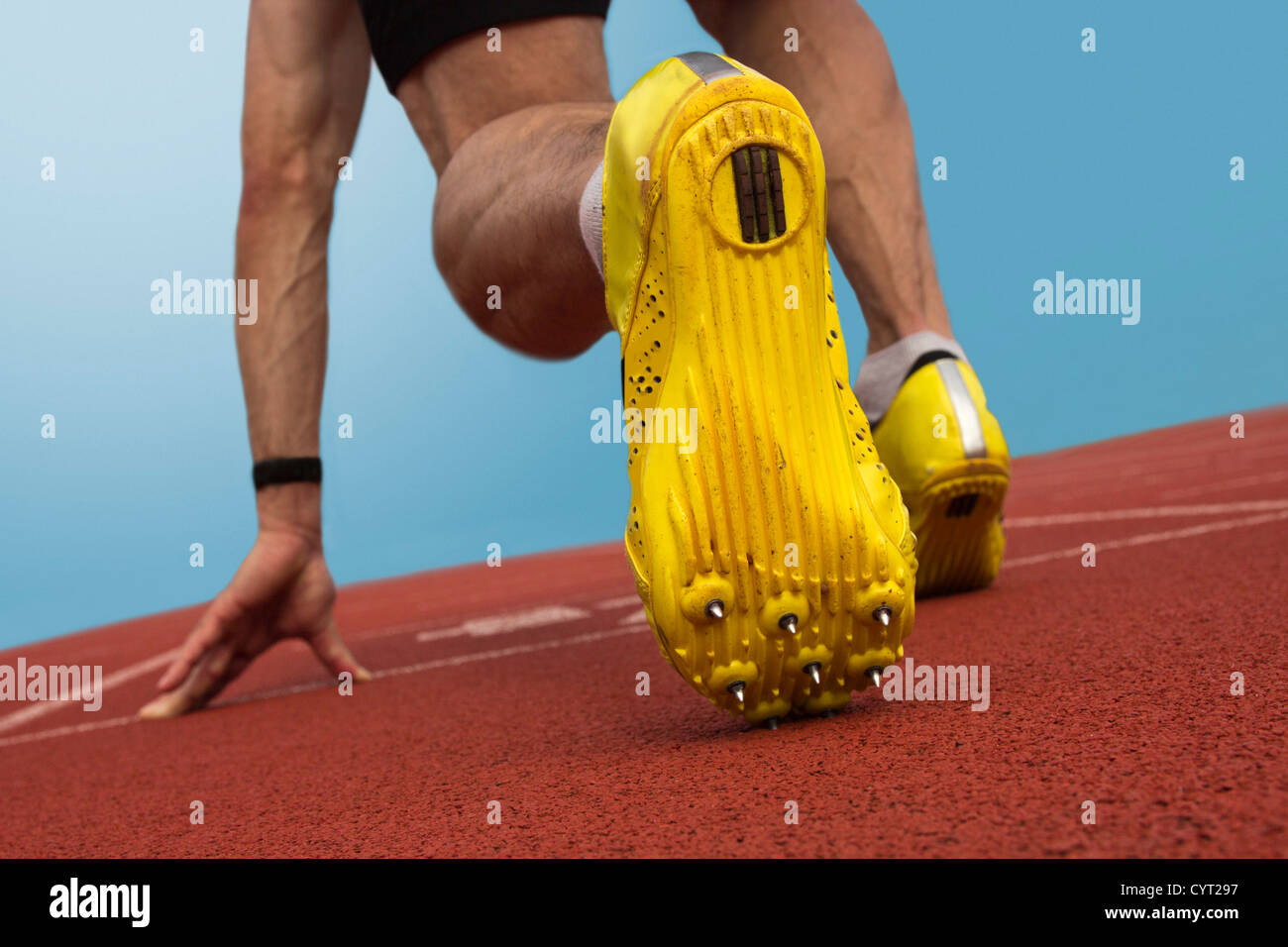 Sprinter with spikes is in start position - Stock Image