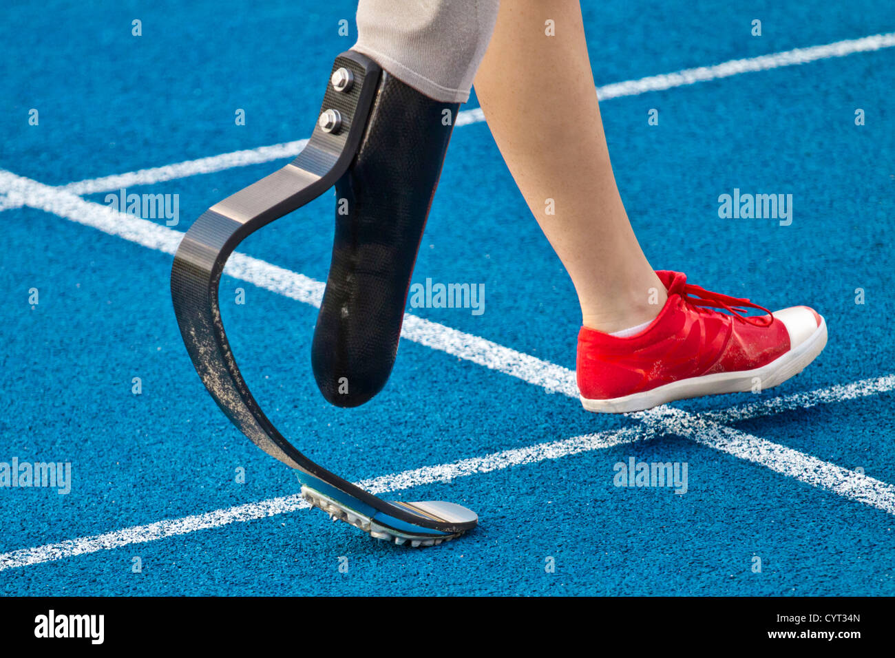 female athlete with handicap is crossing the line - Stock Image