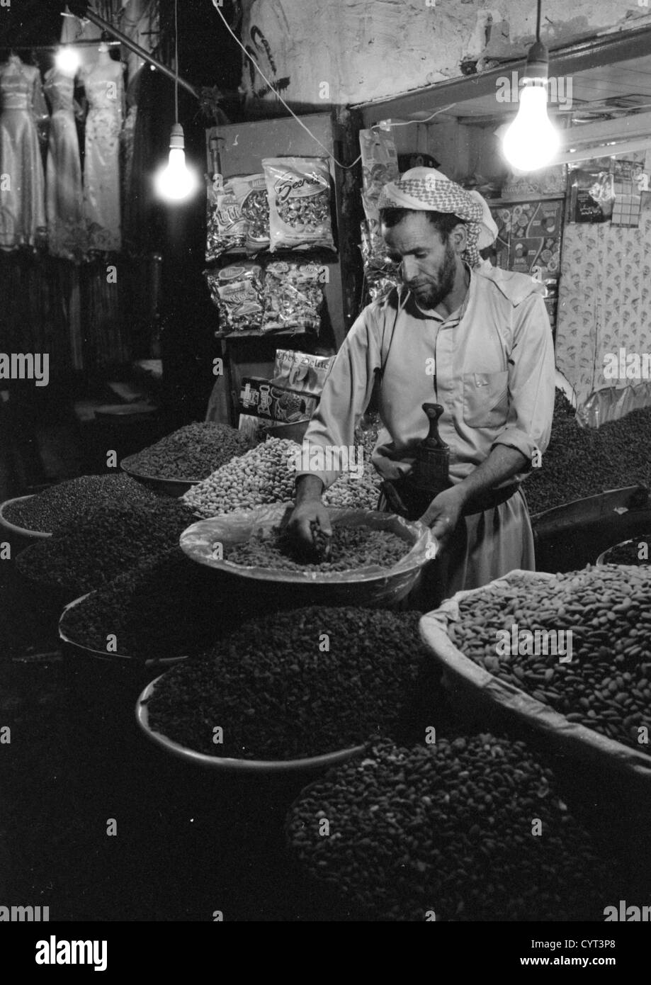 Yemeni Grocer Picking Up Grains In The Souq, Sanaa, Yemen - Stock Image